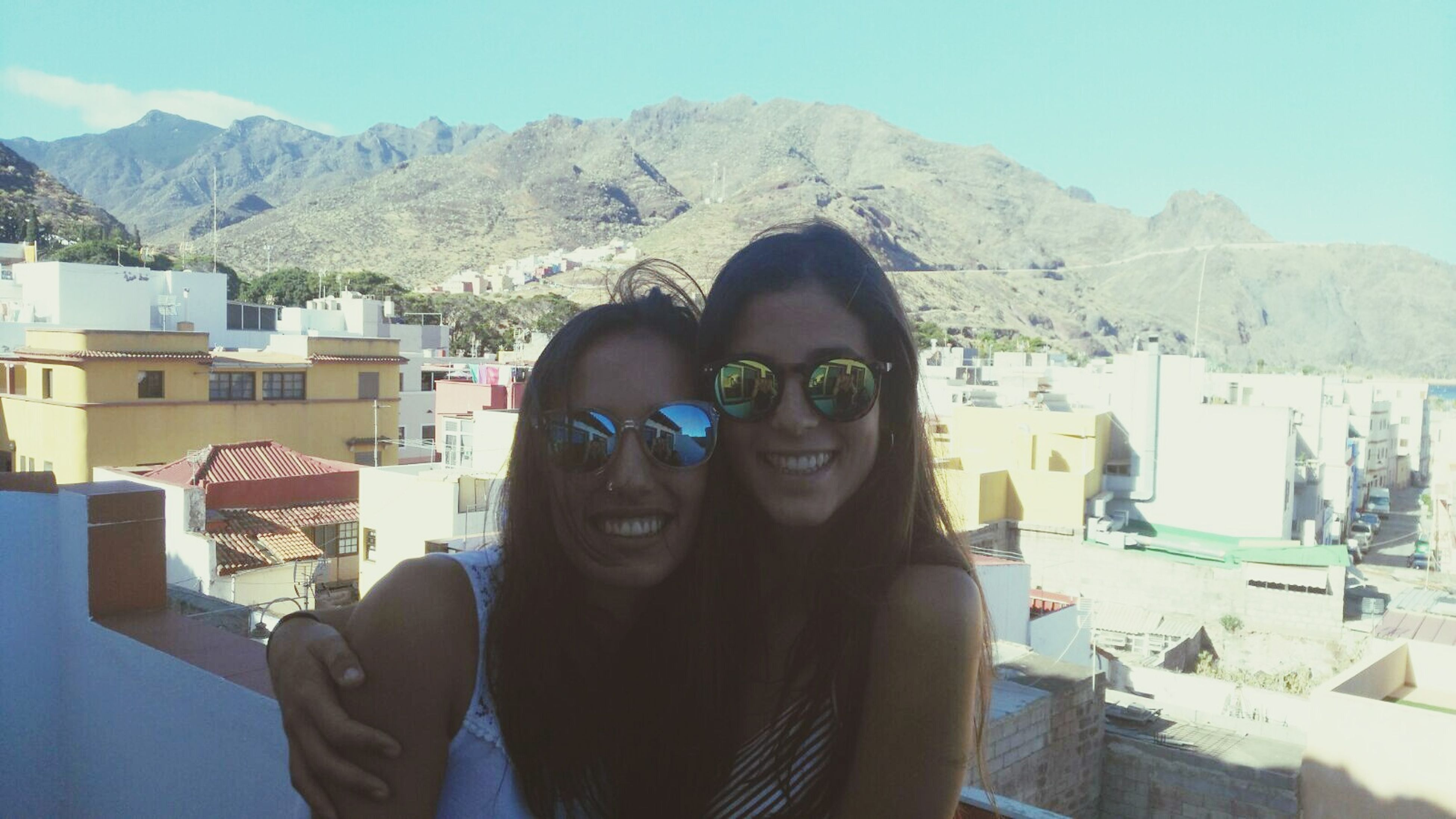 mountain, looking at camera, portrait, young women, toothy smile, leisure activity, friendship, young adult, togetherness, lifestyles, architecture, smiling, building exterior, front view, built structure, sunglasses, enjoyment, long hair, mountain range, fun, friends, mountain peak