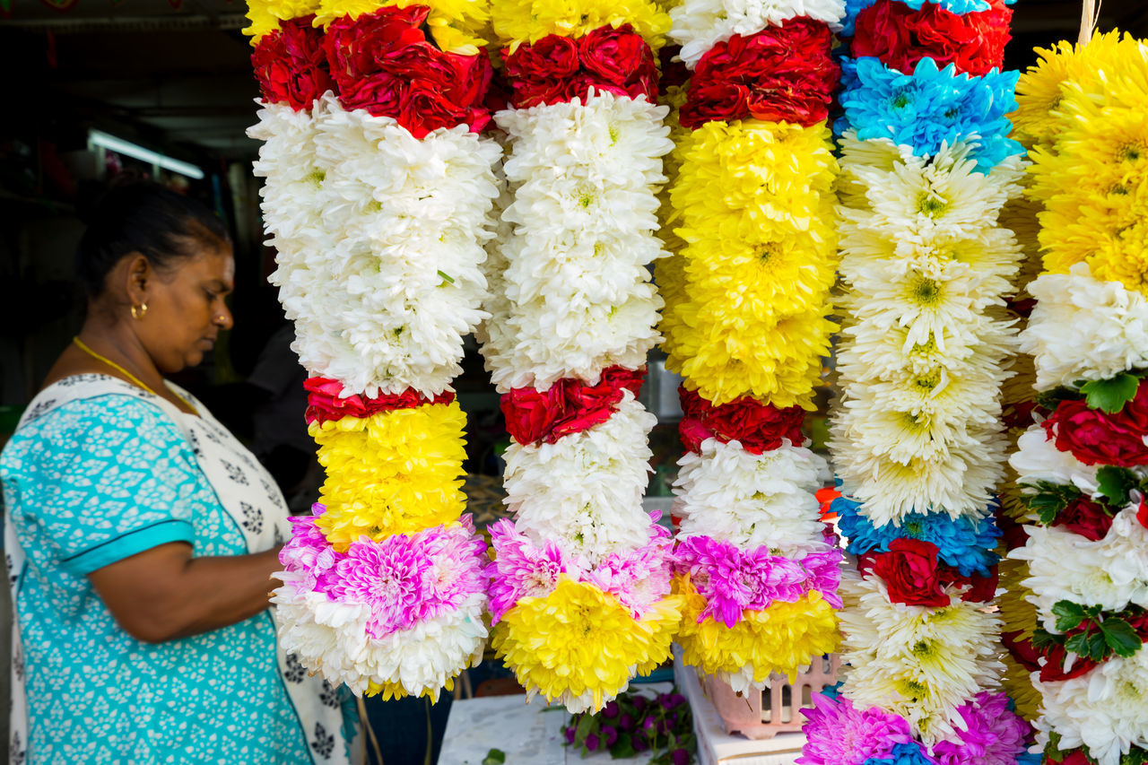 BATU CAVES, MALAYSIA - 9TH FEBRUARY 2017; Hindu devotees performing a pray session during Thaipusam festival in Batu Caves temple, celebrating Lord Murugan victory over the demon Soorapadman. Adult Batu Caves -Malaysia Cultures Day Floral Garland Flower Flower Market Fragility Freshness Garland Hinduism Multi Colored Only Women Outdoors People Real People Sari Standing Thaipusam 2017 Yellow