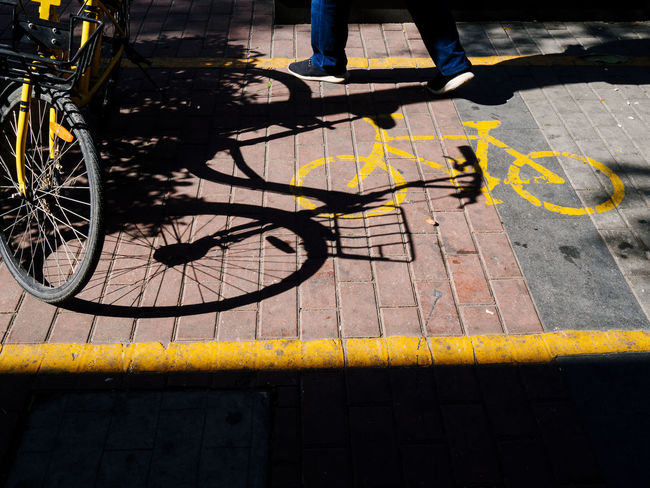 Bicycle Bicycle Rack City Day High Angle View Human Leg Land Vehicle Low Section Mode Of Transport One Person Outdoors People Real People Sidewalk Stationary Street Sunlight Transportation Yellow