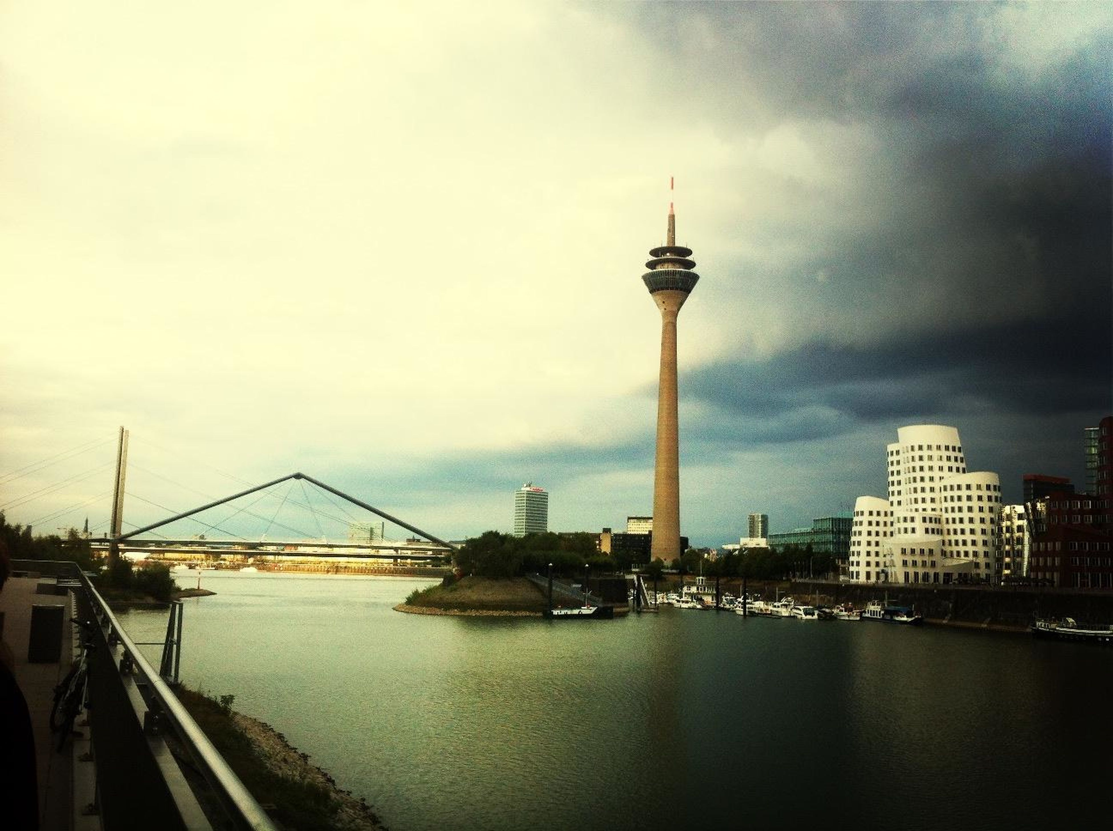 architecture, built structure, sky, building exterior, city, water, cloud - sky, tower, tall - high, communications tower, river, travel destinations, international landmark, capital cities, cloudy, famous place, cityscape, waterfront, travel, tourism