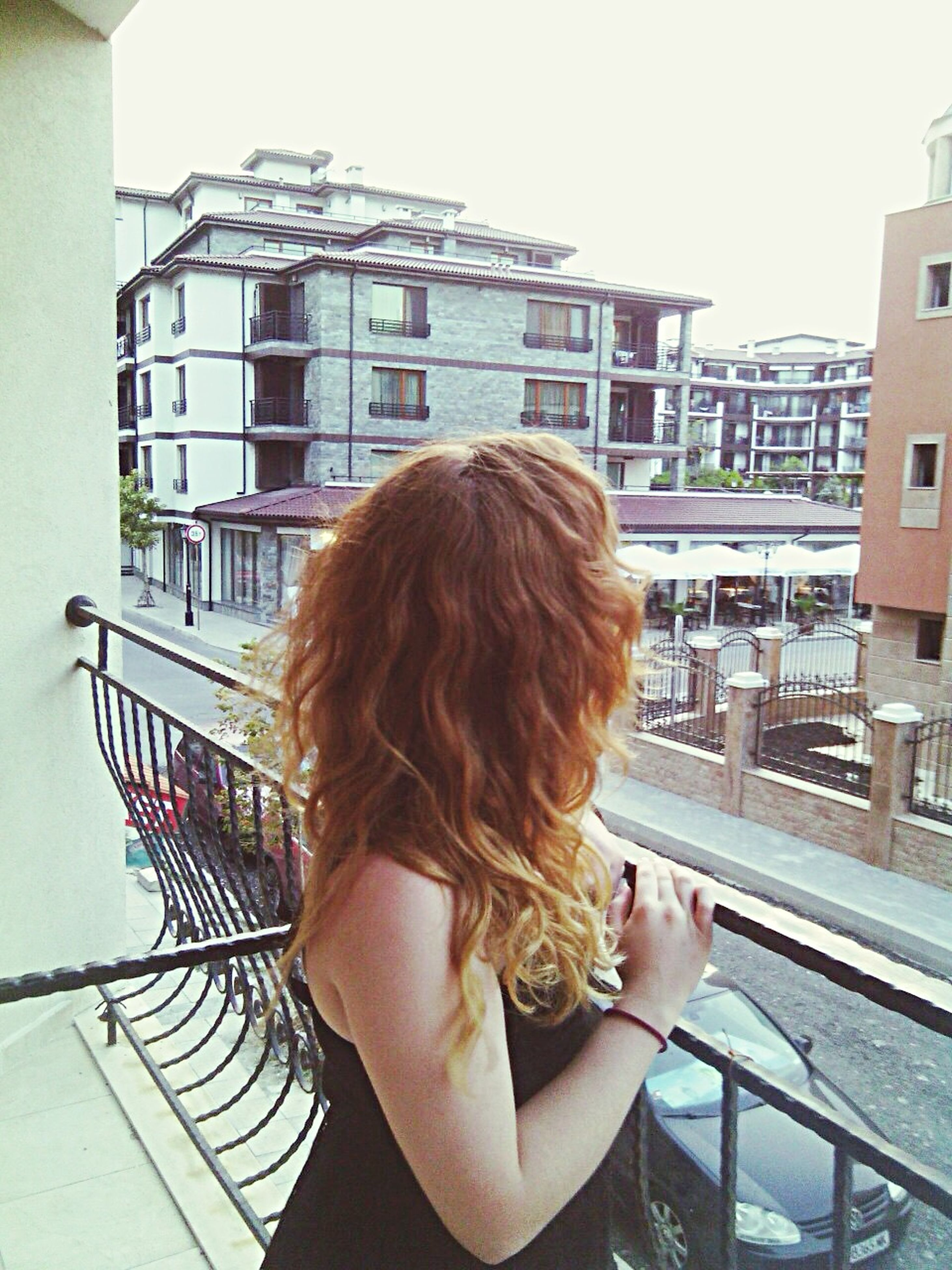 architecture, lifestyles, built structure, building exterior, railing, leisure activity, young adult, casual clothing, person, young women, long hair, standing, rear view, building, waist up, sitting, city