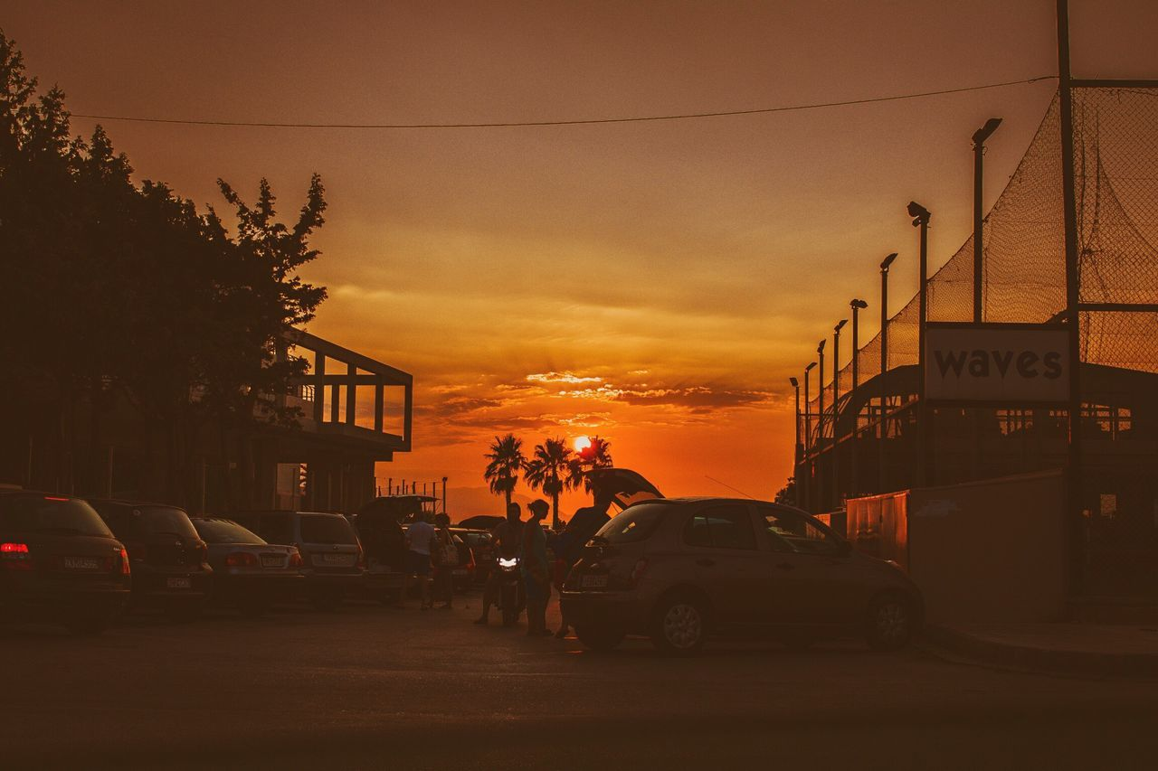 car, sunset, land vehicle, transportation, mode of transport, architecture, street, city, sky, cloud - sky, building exterior, outdoors, built structure, real people, one person, tree, people