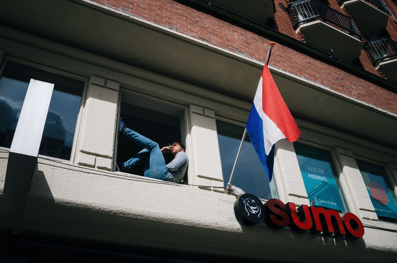 The man sits in the window frame and smokes. Amsterdam, Netherlands. Amsterdam Architecture Building Exterior Dutch Flag Full Length Holland Lifestyles Low Angle View Man Netherlands One Person Real People Smoke Window Window Frame The Street Photographer - 2017 EyeEm Awards