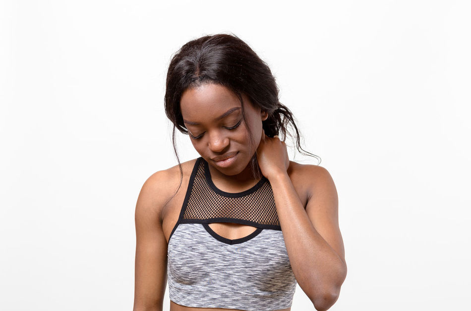 Adult Adults Only Day Exercising Eyes Closed  Front View Healthy Lifestyle Lifestyles Looking Down One Person One Woman Only One Young Woman Only Only Women People Self Improvement Sports Clothing Standing Studio Shot Waist Up White Background Young Adult