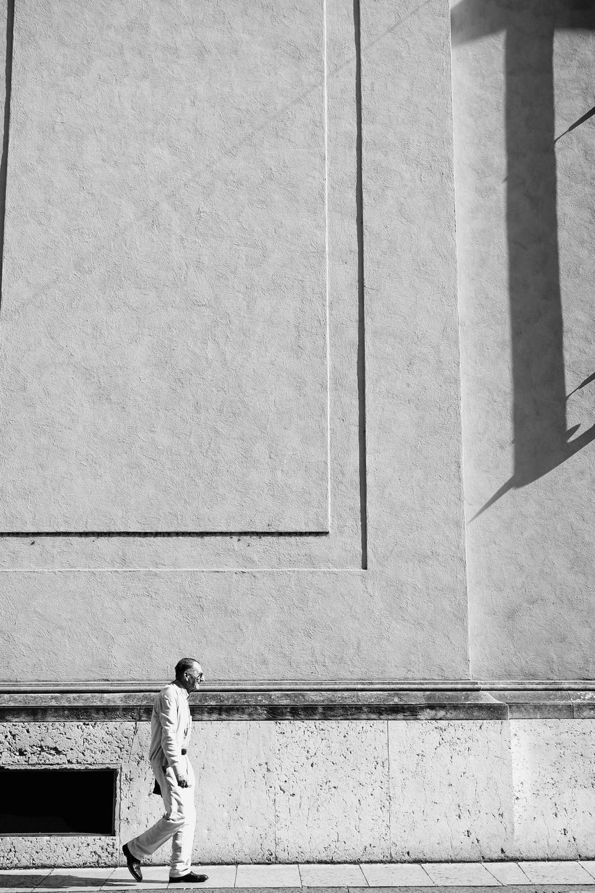 Senior Man Walking By Building