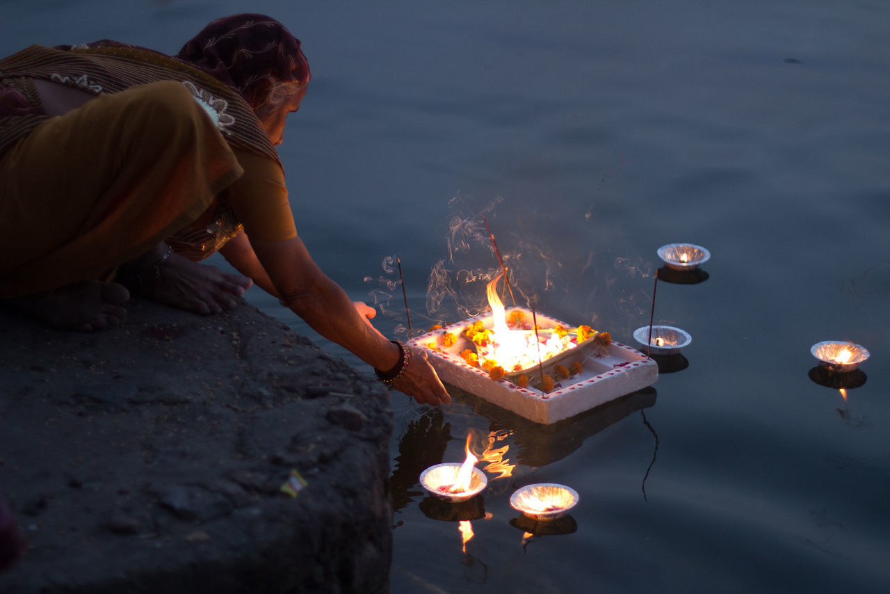 Side view of a woman leaving offerings in water