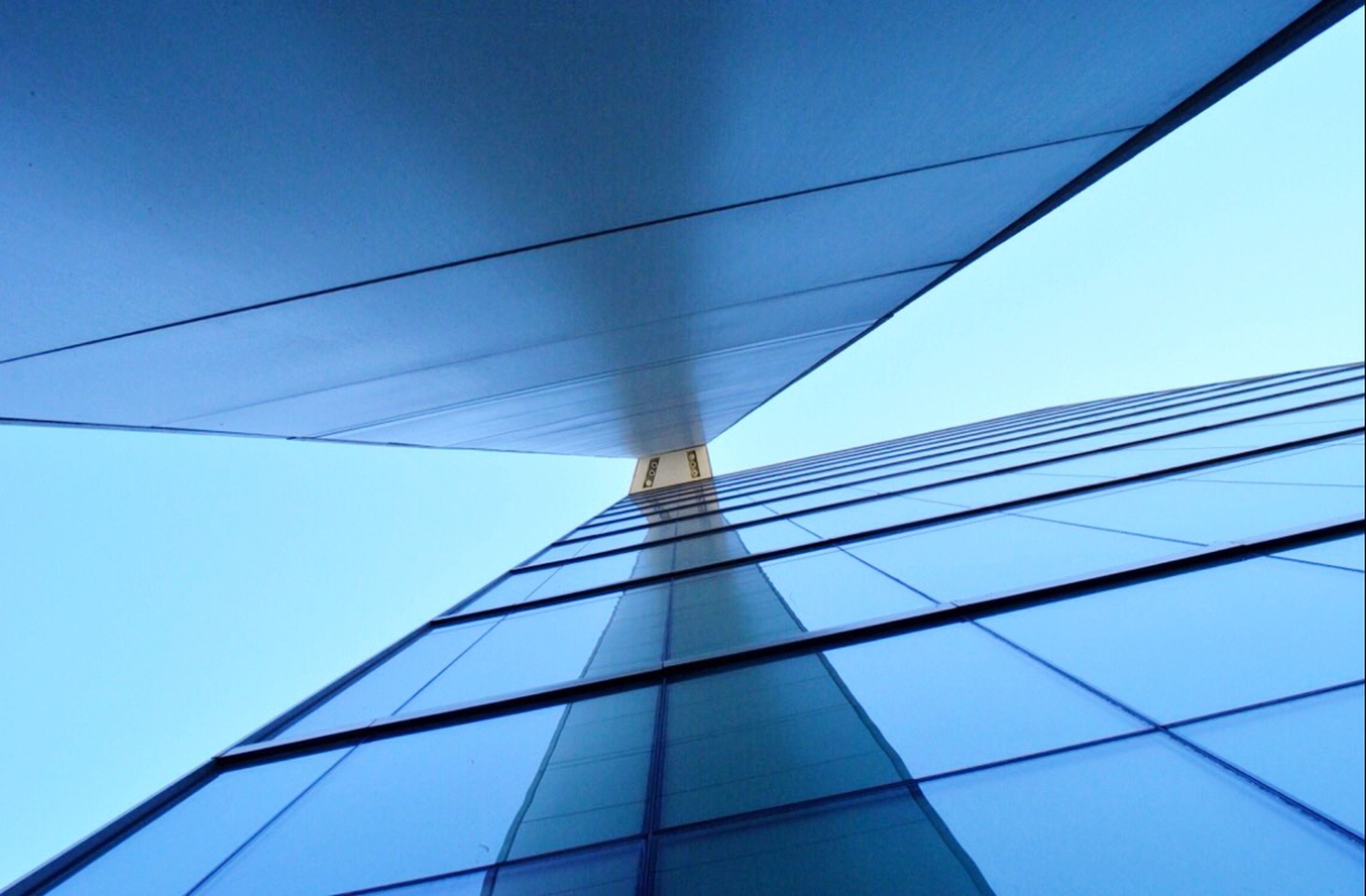 low angle view, architecture, built structure, blue, clear sky, modern, building exterior, office building, connection, sky, tall - high, day, city, outdoors, no people, cable, building, glass - material, tower, reflection