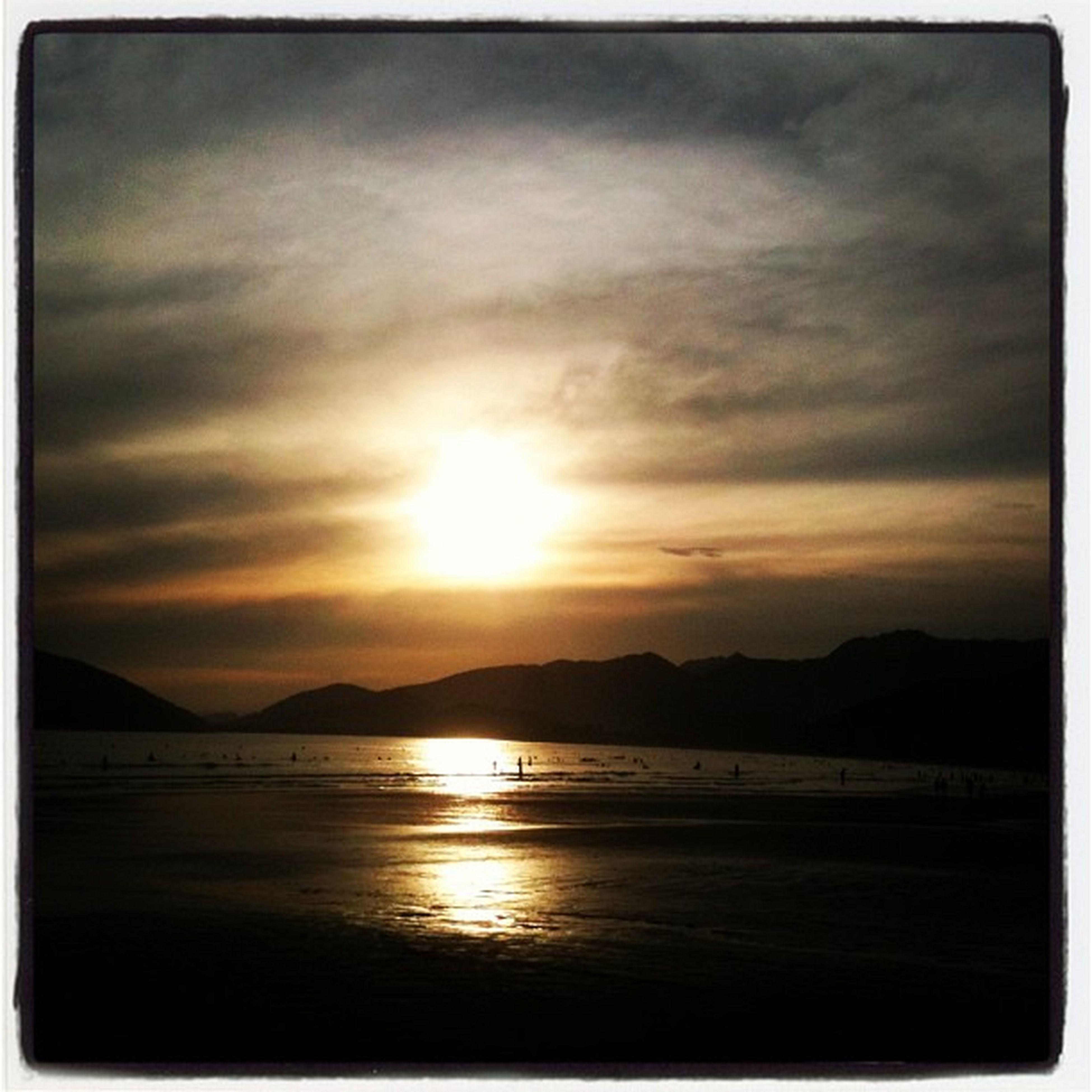 sunset, water, scenics, tranquil scene, sun, beauty in nature, sky, tranquility, mountain, transfer print, sea, reflection, nature, cloud - sky, idyllic, mountain range, auto post production filter, sunlight, cloud, sunbeam