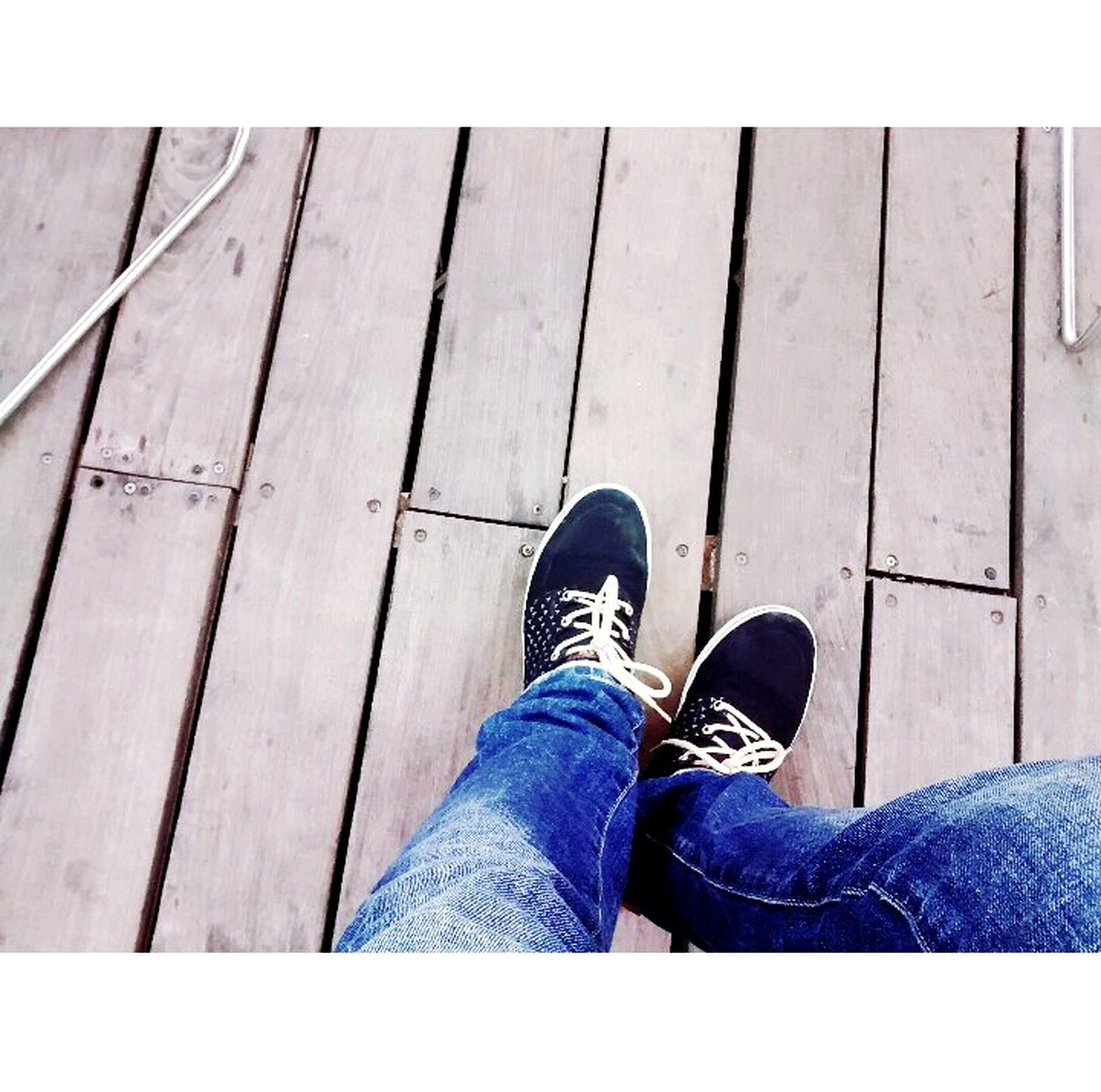low section, person, shoe, jeans, personal perspective, human foot, lifestyles, standing, footwear, relaxation, men, high angle view, blue, leisure activity, wood - material, casual clothing, sitting