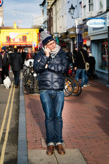 A real life elf... Adult Blue Bobble Hat  Brighton Busy Street FreshonEyeem Jeans Leaning Listening Man Mobile Phone Outdoors Pavement Road Shopping Street Street Photography Streetphoto_color Talking On The Phone The Lanes Vibrant Vibrant Color Woolly Hat Yellow Lines