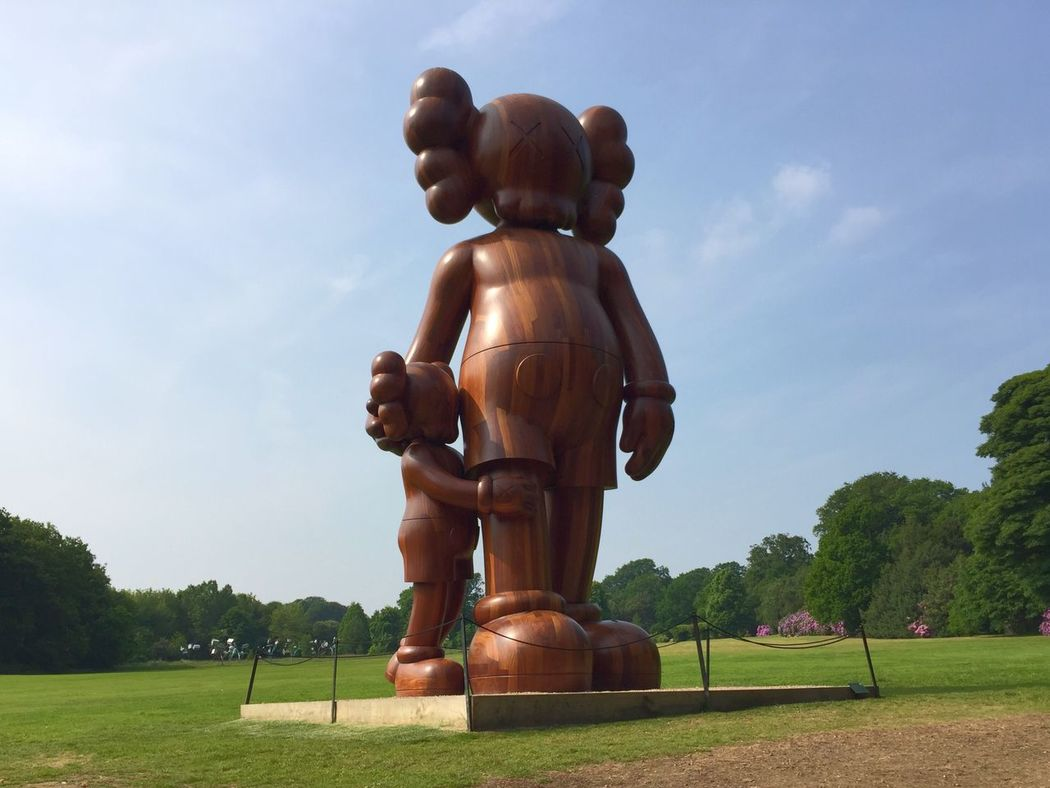 Tree Grass Sculpture Lawn Art Park - Man Made Space Sky Day Famous Place Tranquil Scene Green Color Grassland Outdoors Creativity Park Tourism Footpath Topiary Rural Scene kaws