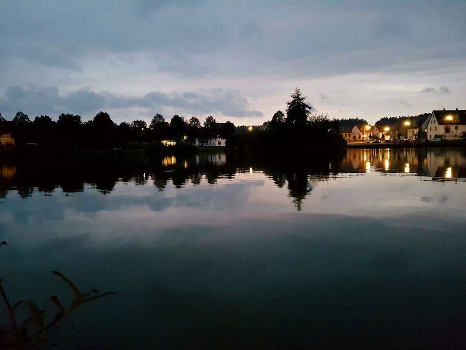 Reflection Water Lake Building Exterior Tree Built Structure Calm Silhouette Dusk Nature Beauty In Nature Tranquil Scene Architecture Illuminated Tranquility Sky Scenics Mid Distance Standing Water Waterfront Cloud Cloud - Sky