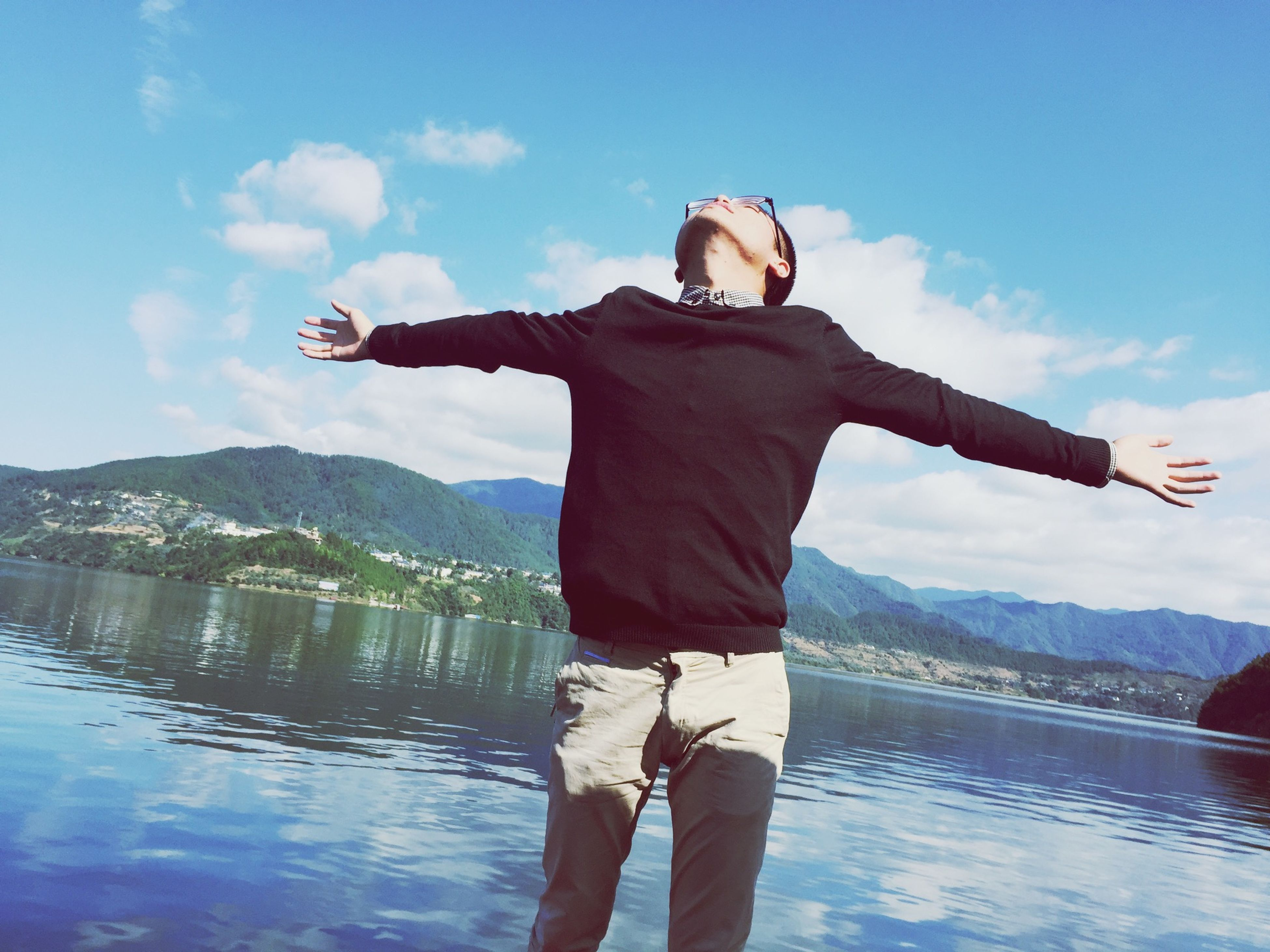 lifestyles, full length, water, casual clothing, standing, leisure activity, sky, young adult, lake, three quarter length, rear view, cloud - sky, mountain, arms outstretched, person, young men, mountain range, tranquil scene