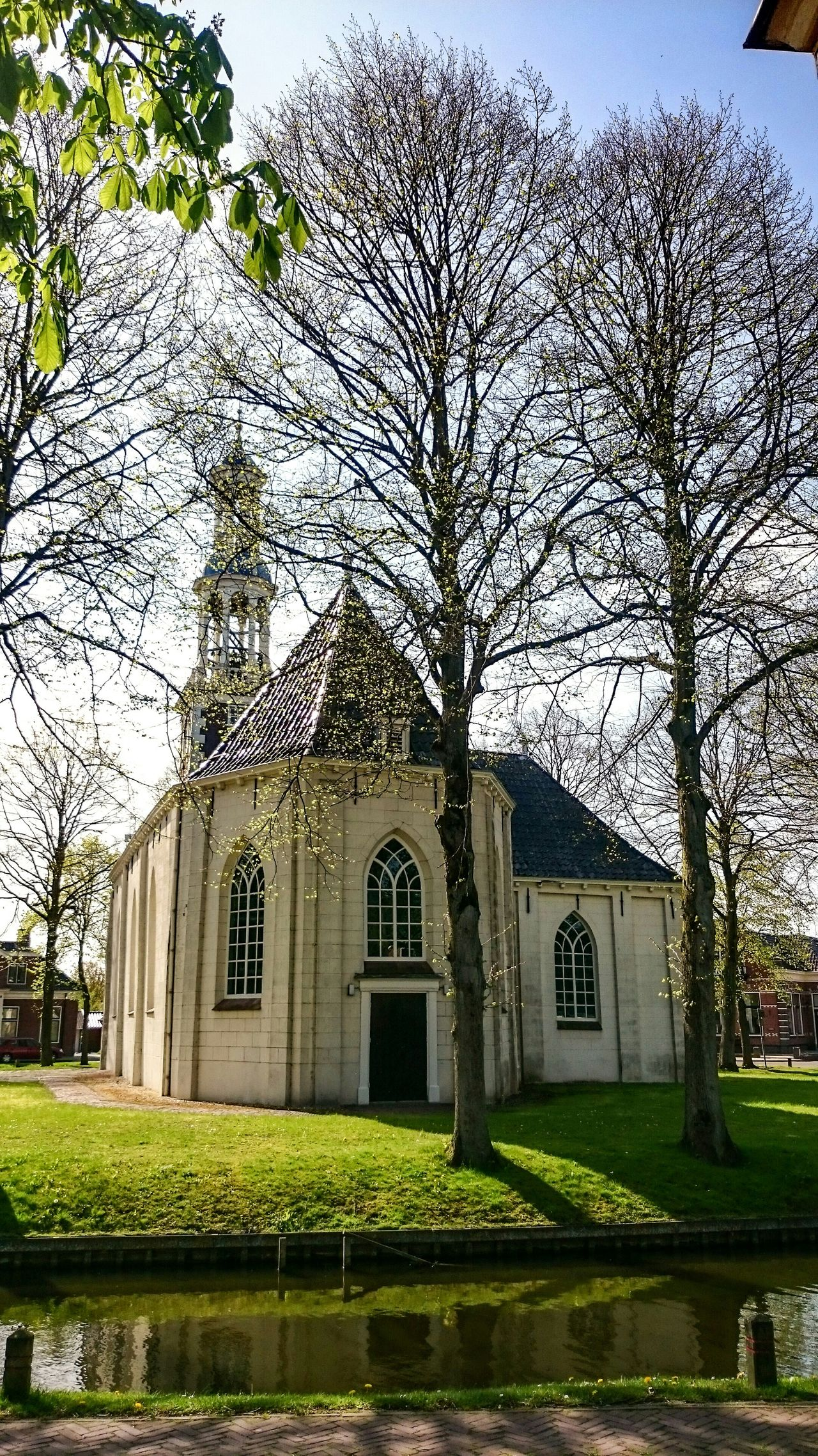 In My Village Spijk. Old Church surrounded by Trees, Sunshine Reflections on the roof. On a warm Sunday Afternoon