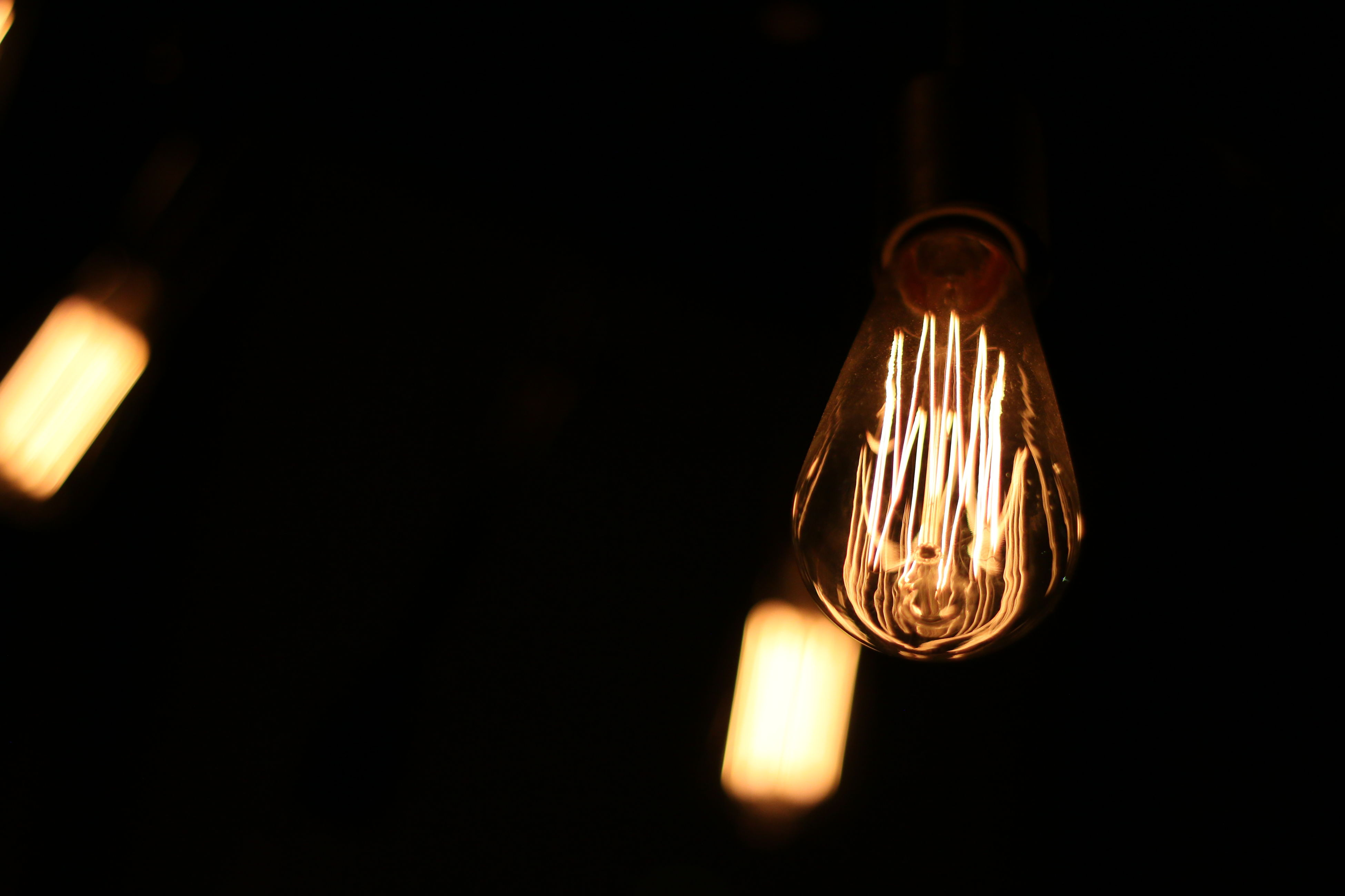 lighting equipment, electricity, illuminated, light bulb, low angle view, glowing, hanging, close-up, no people, filament, indoors, technology, night, darkroom