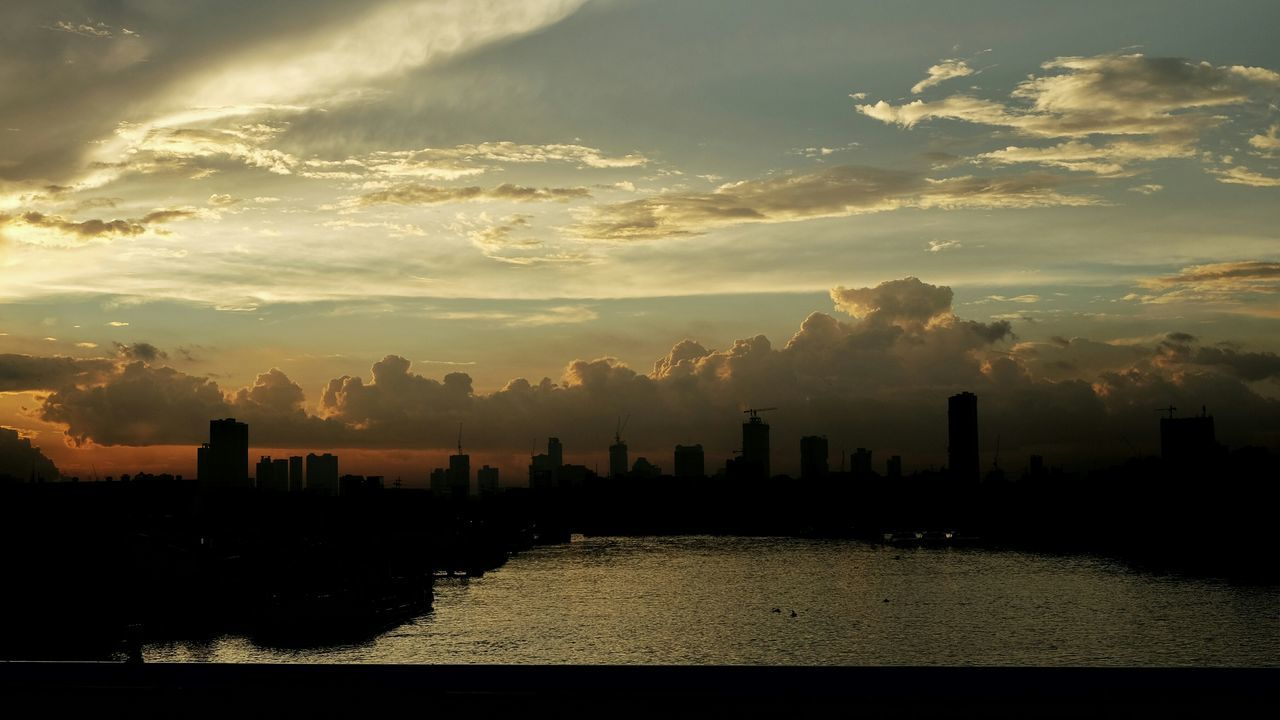 skyscraper, sunset, architecture, city, building exterior, built structure, cityscape, no people, sky, sunlight, waterfront, urban skyline, outdoors, river, travel destinations, downtown district, cloud - sky, water, modern, growth, nature, beauty in nature, day