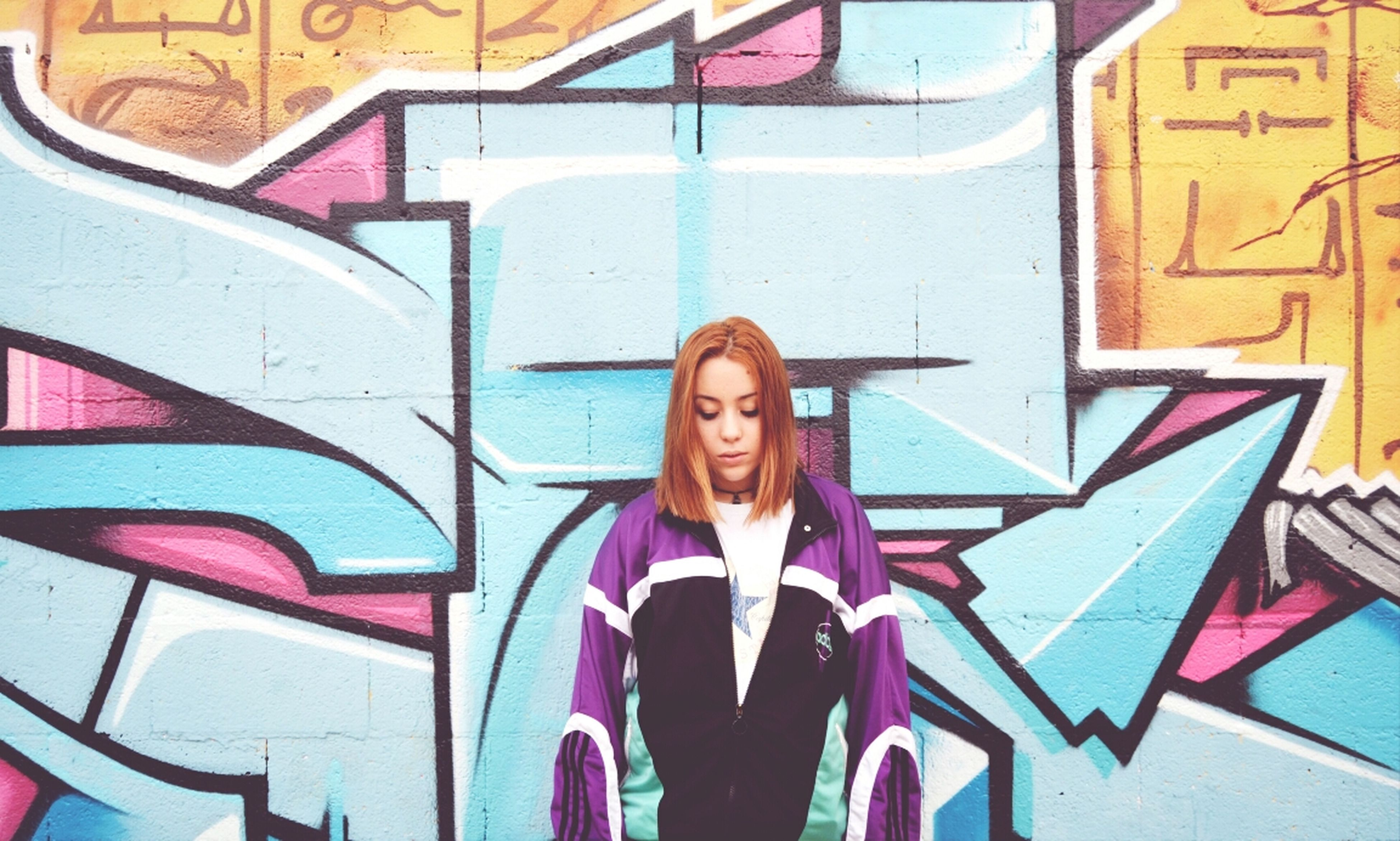 graffiti, young adult, art, looking at camera, front view, creativity, wall - building feature, portrait, person, art and craft, lifestyles, young women, architecture, smiling, casual clothing, built structure, standing, human representation