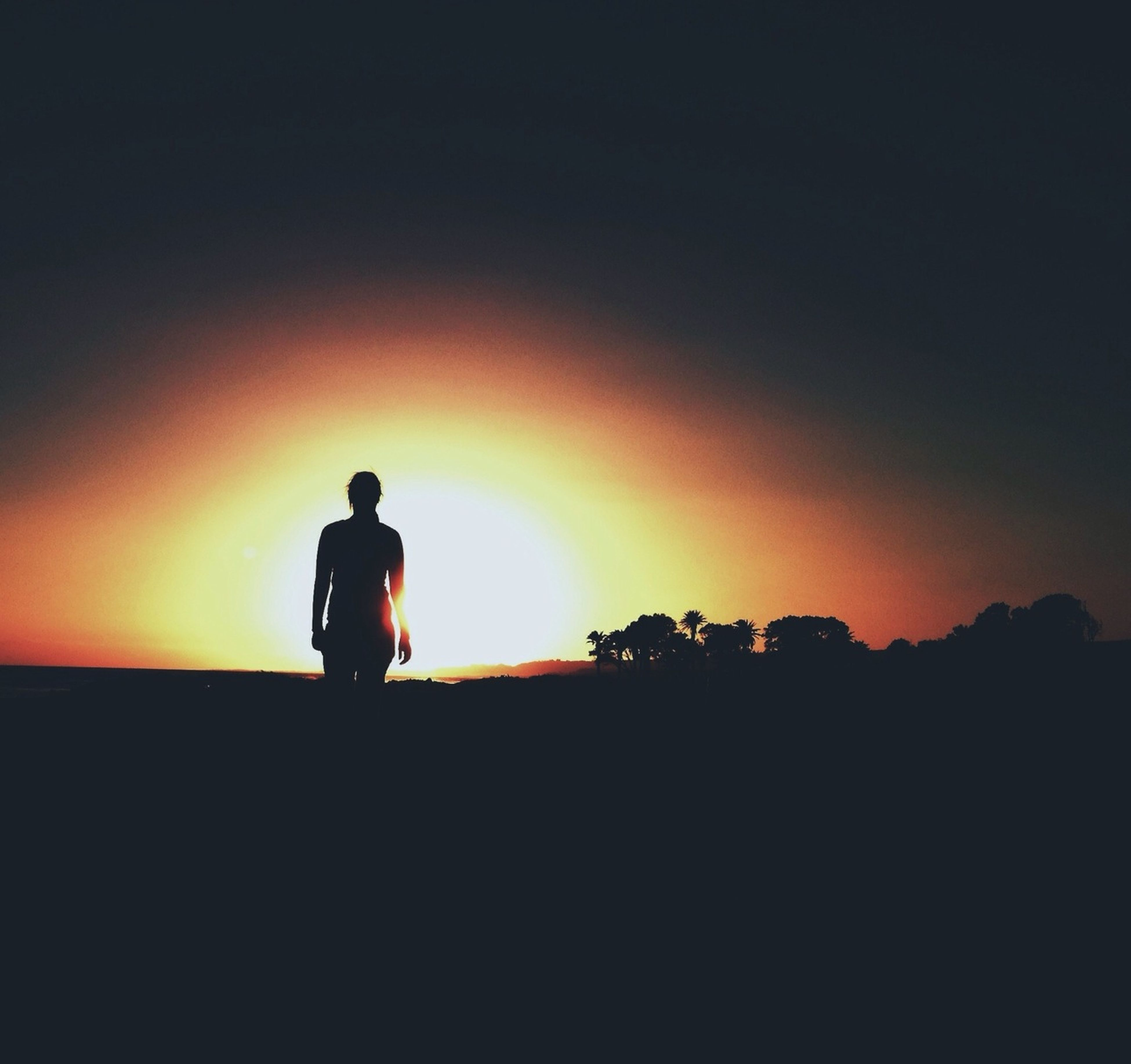 silhouette, sunset, sun, orange color, copy space, men, lifestyles, leisure activity, scenics, tranquil scene, standing, beauty in nature, tranquility, outline, sky, idyllic, nature, clear sky
