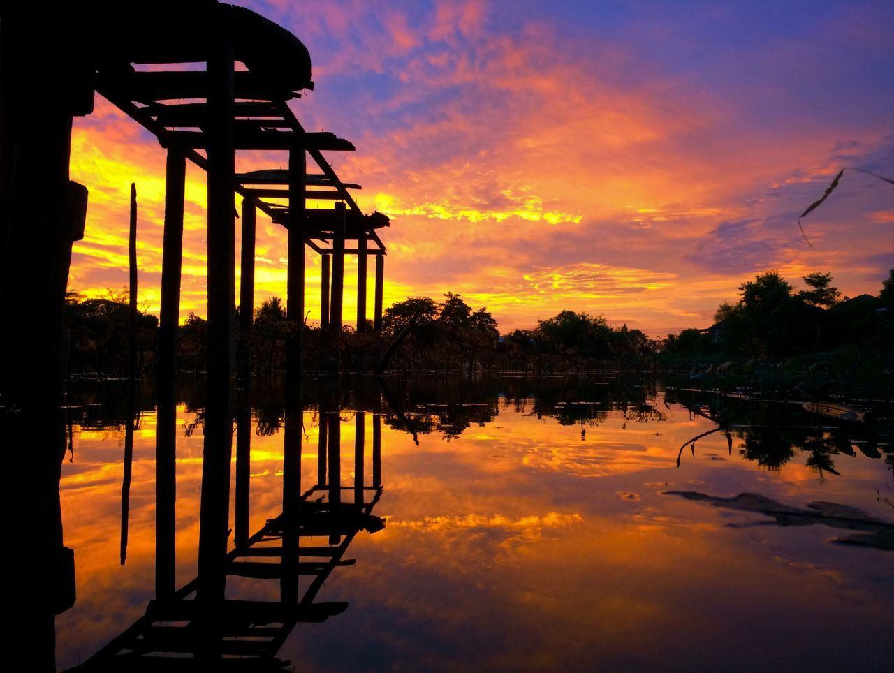 sunset, reflection, water, orange color, silhouette, scenics, lake, standing water, built structure, idyllic, sky, tree, cloud - sky, tranquil scene, beauty in nature, pier, cloud, tranquility, waterfront, dramatic sky, majestic, remote, red, outdoors, nature, calm, non-urban scene, vibrant color, architectural column, romantic sky, atmospheric mood