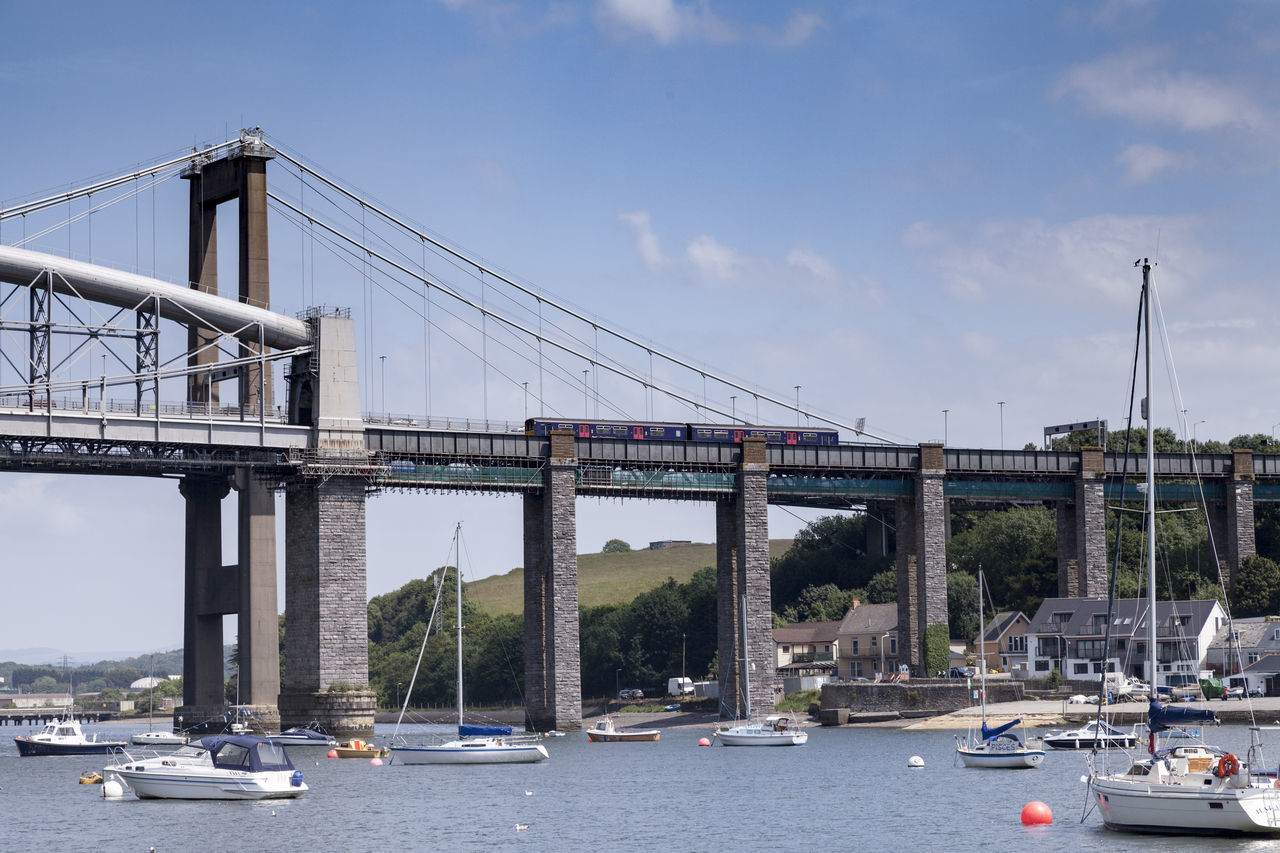 A train crosses the Tamar Rail Bridge from Plymouth to Cornwall, as seen from the river Architecture Bridge Bridge - Man Made Structure Built Structure City Connection Day Mode Of Transport No People Outdoors River River Tamar Tamar Bridge Tamar Rail Bridge Train Transportation Water
