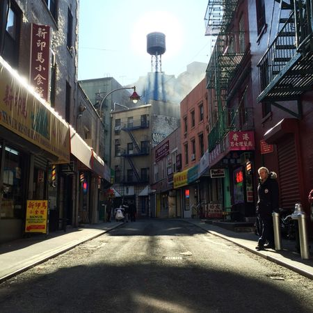 Chinatown street with water tower Chasinglight Light And Shadow Sun Water Tower Chinatown New York City Streetphotography Street Dirty Chinese Culture Doyers Street