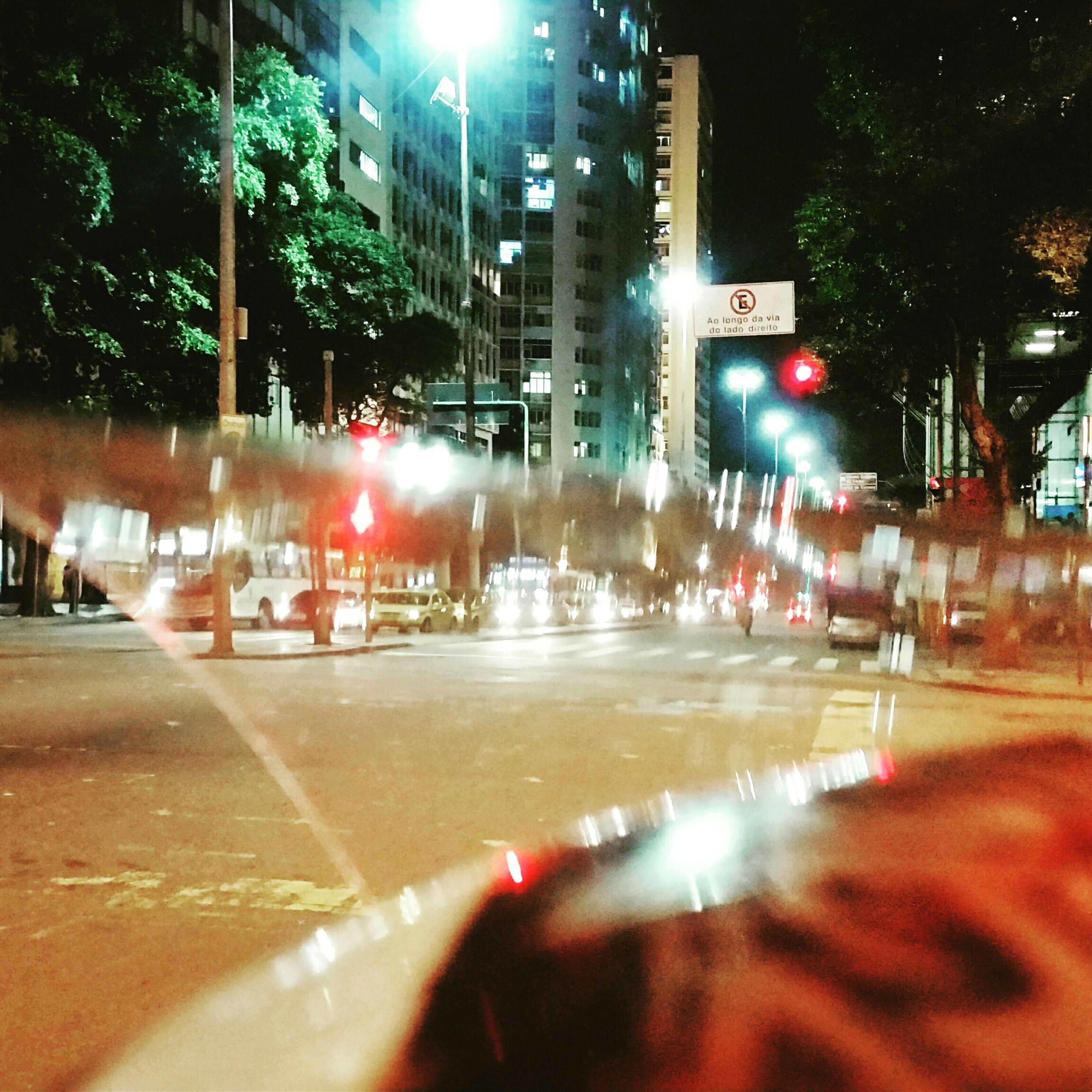 illuminated, city, building exterior, night, street, city street, architecture, city life, built structure, car, transportation, road, street light, motion, land vehicle, traffic, incidental people, blurred motion, zebra crossing