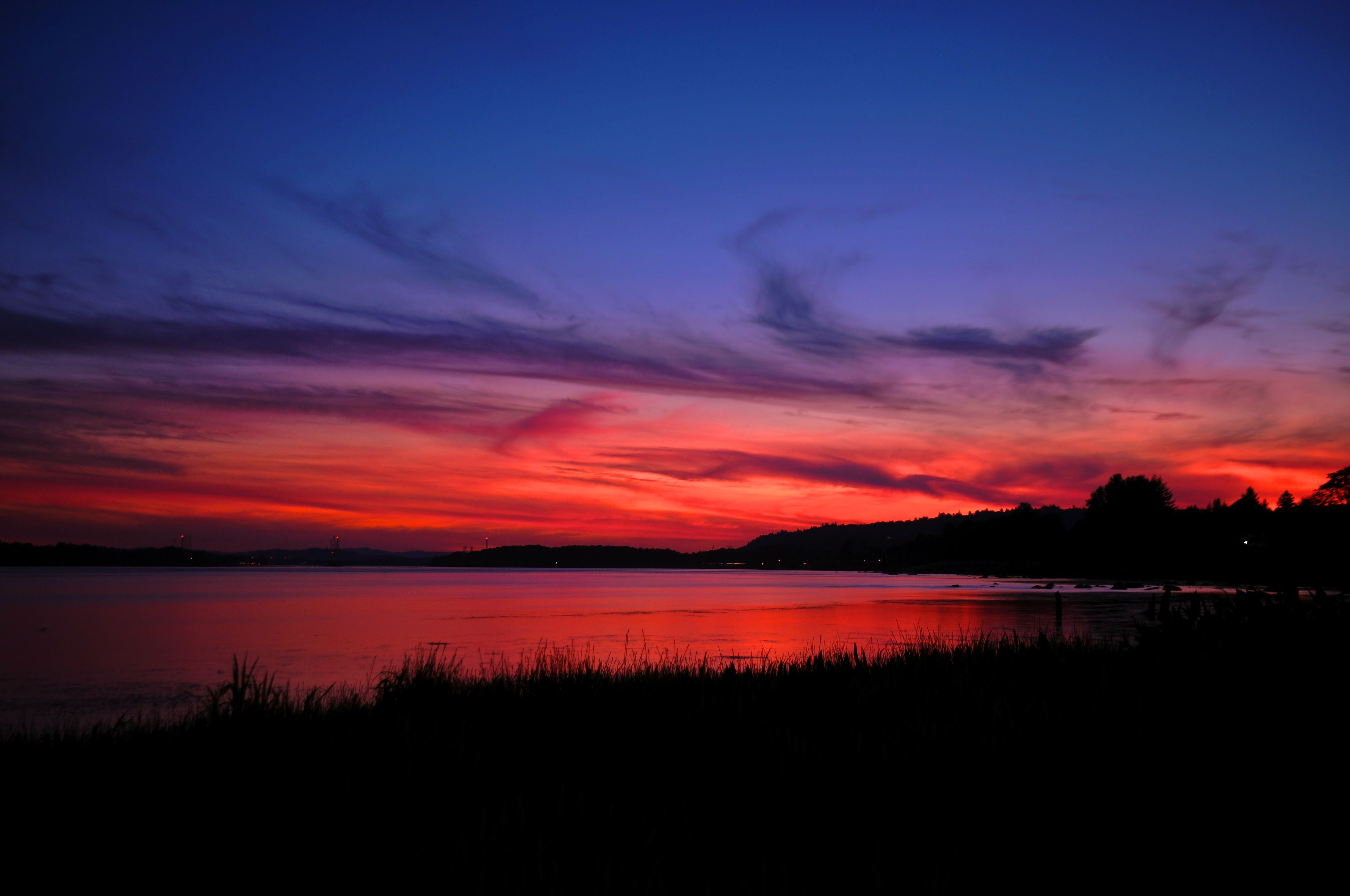 sunset, scenics, tranquil scene, water, silhouette, tranquility, lake, beauty in nature, sky, dusk, non-urban scene, idyllic, dramatic sky, majestic, nature, romantic sky, blue, cloud - sky, tourism, travel destinations, atmospheric mood, orange color, atmosphere, plant, vacations, cloud, dark, vibrant color, moody sky, outdoors, countryside, calm