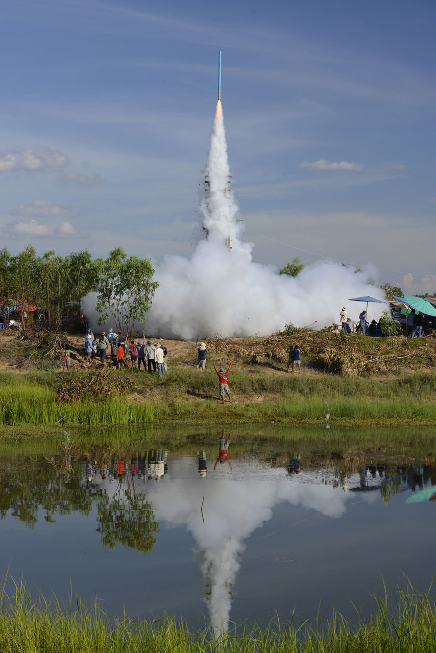 Group Of People Watching Rocket Launch On Landscape