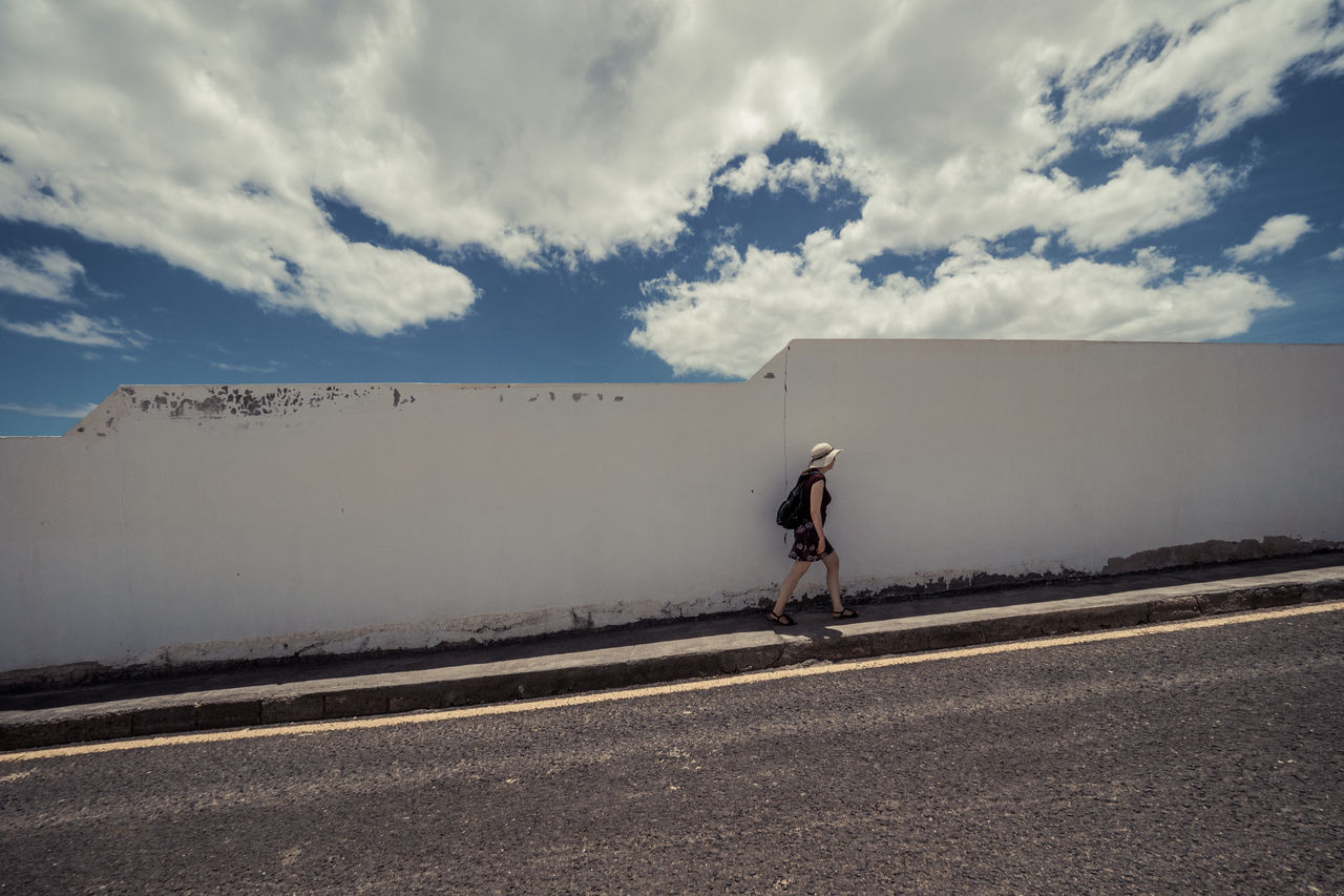 A woman walks on a street in front of a white wall with a cloudy sky Adult Cloud - Sky Day One Person Outdoors People Real People Road Sky Young Adult