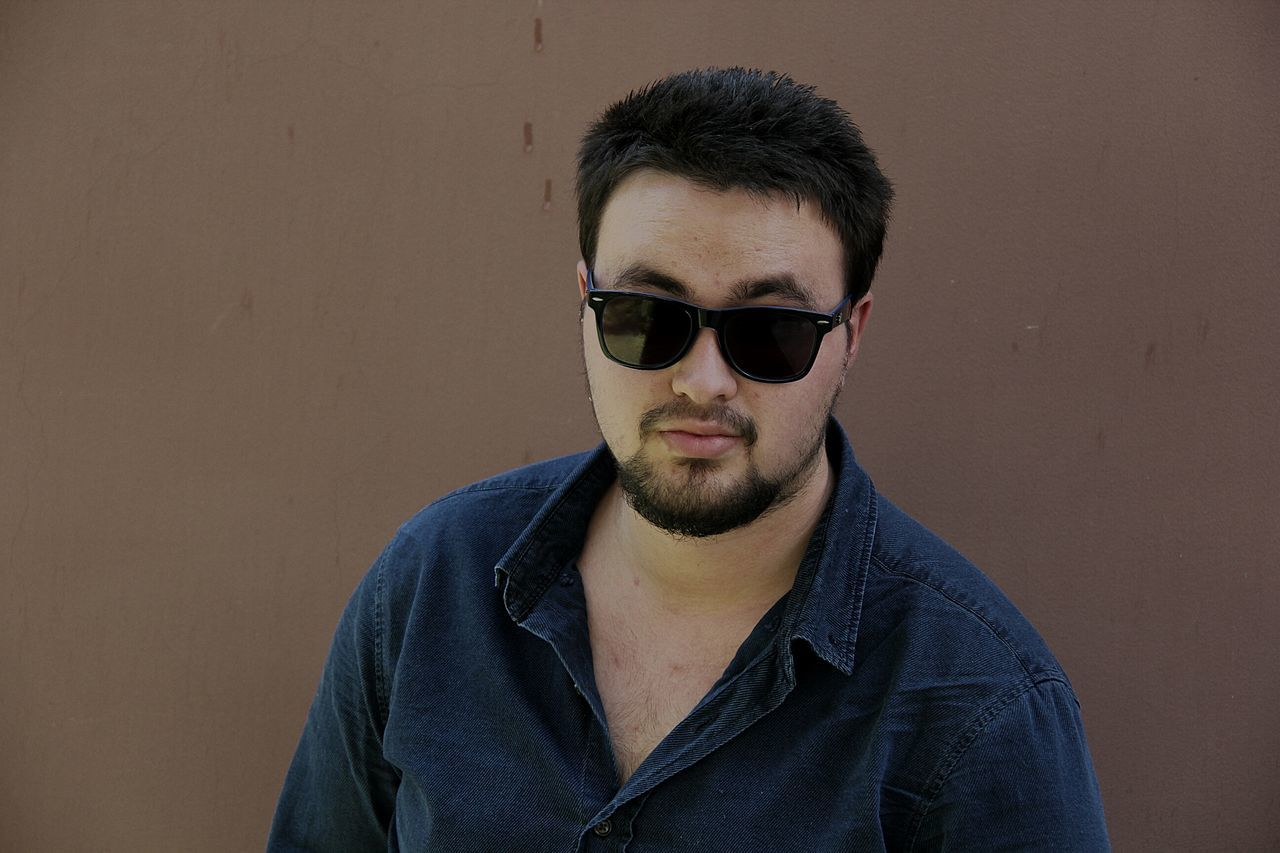 Portrait Of Young Man Wearing Sunglasses Against Wall