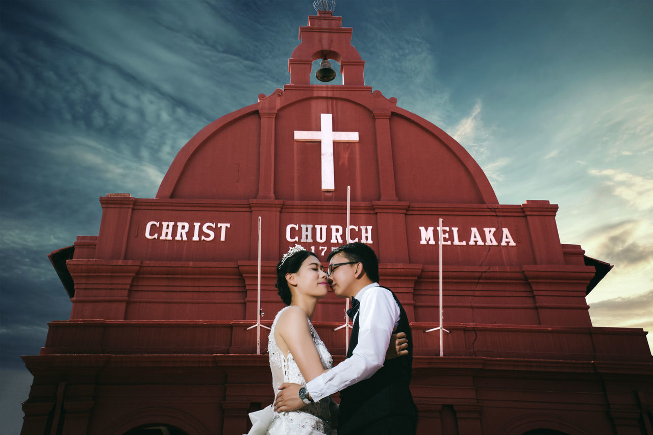 Bride And Groom Embracing In Front Of Church Against Sky