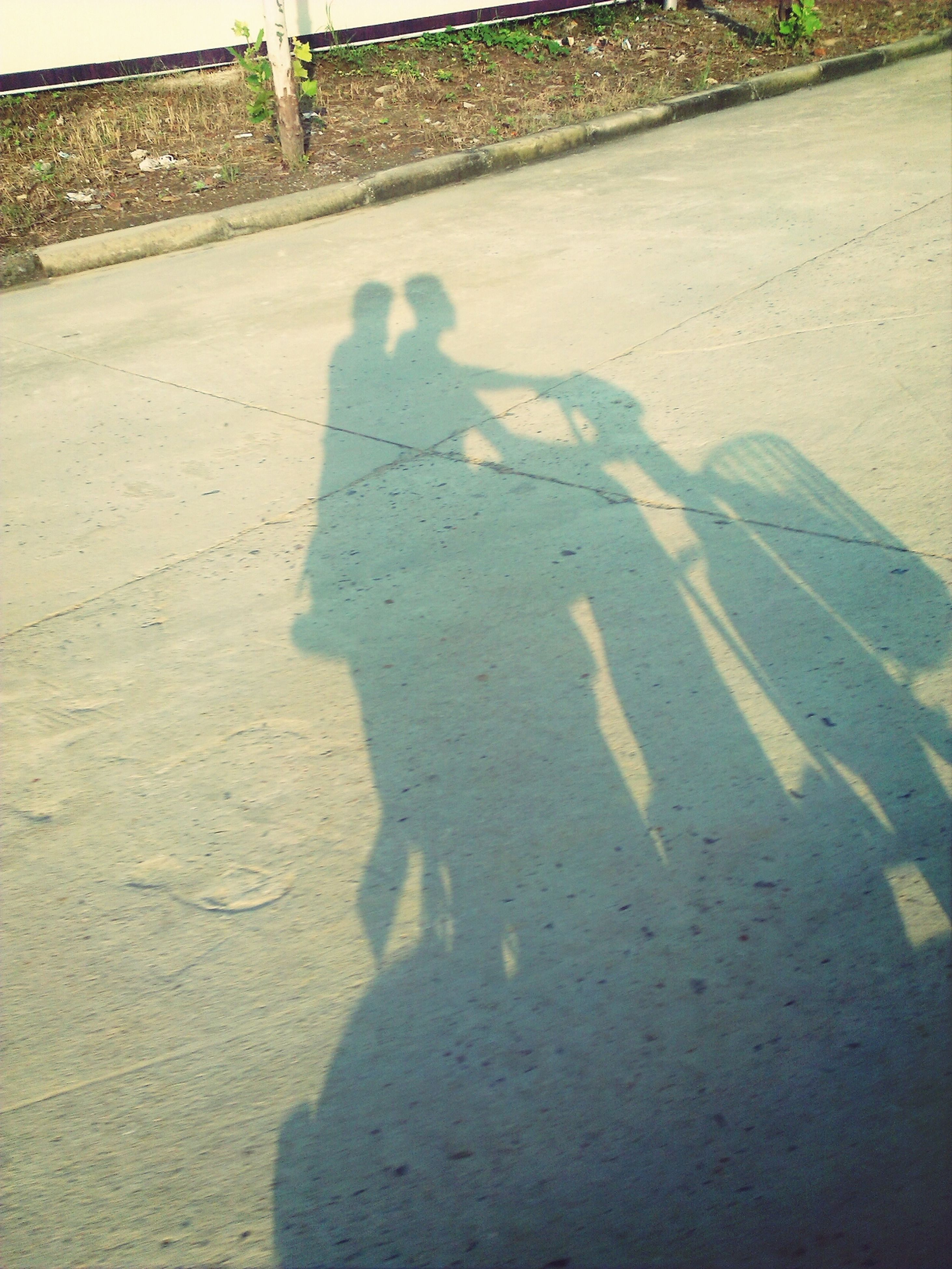 shadow, road, sunlight, high angle view, street, asphalt, road marking, transportation, day, outdoors, the way forward, guidance, focus on shadow, built structure, no people, grass, sunny, architecture, direction, textured