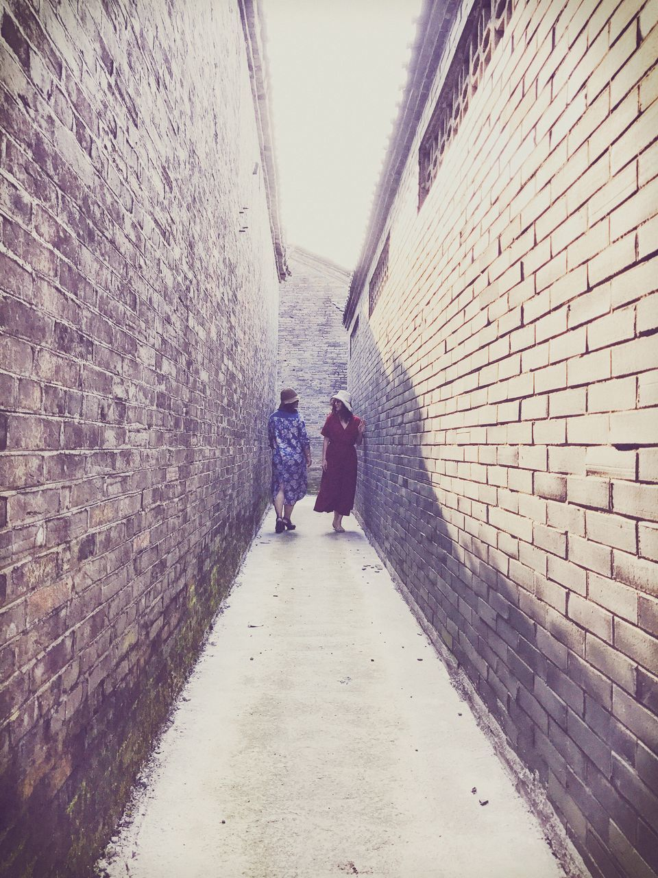 brick wall, real people, architecture, full length, walking, the way forward, built structure, rear view, two people, day, togetherness, lifestyles, men, standing, building exterior, indoors, people