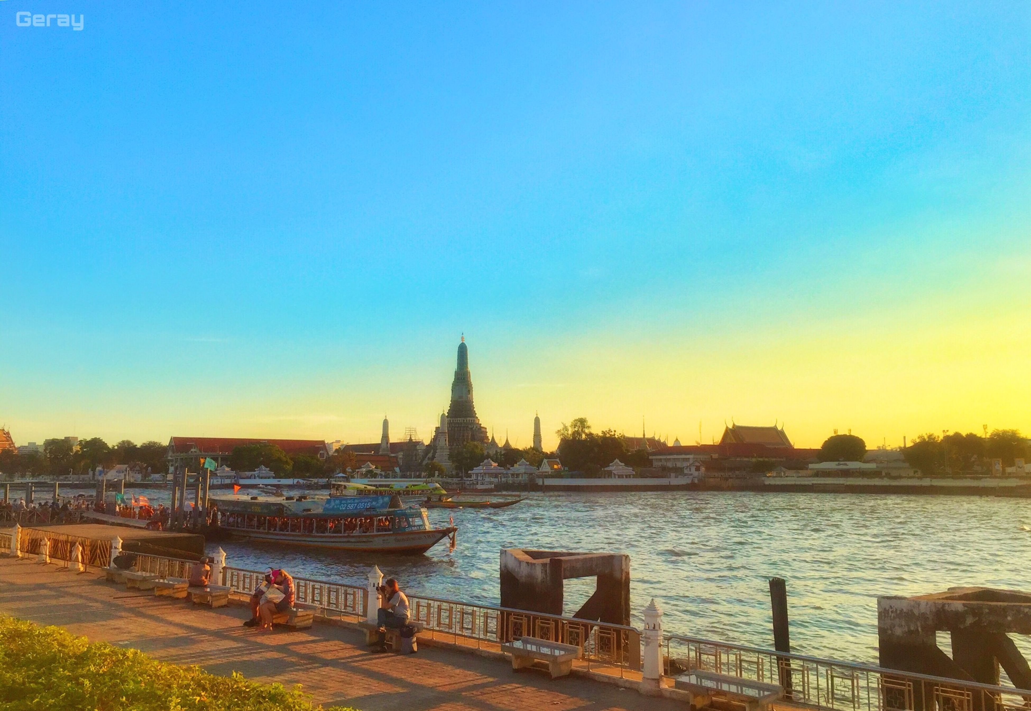 water, clear sky, built structure, architecture, copy space, building exterior, blue, transportation, nautical vessel, sea, mode of transport, boat, river, railing, sky, moored, outdoors, incidental people, city, sunset