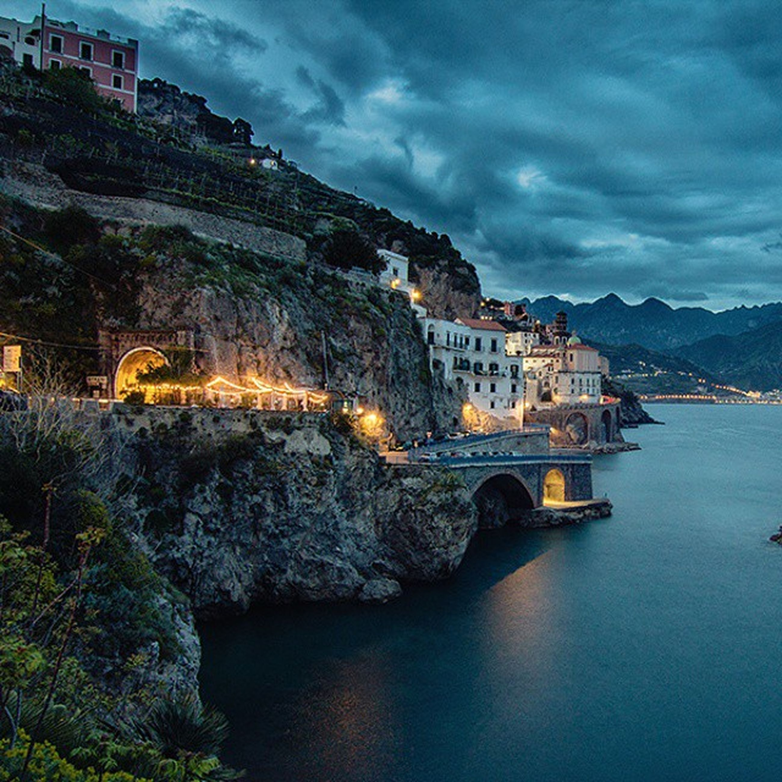 architecture, built structure, water, building exterior, sky, cloud - sky, waterfront, river, mountain, cloudy, residential structure, house, cloud, residential building, sea, town, city, reflection, rock - object, nature