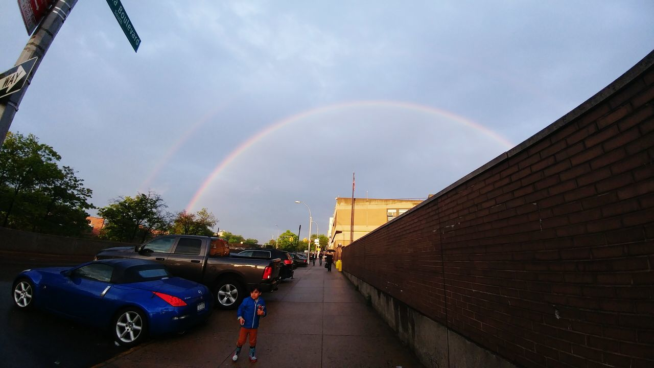 rainbow, car, building exterior, double rainbow, architecture, built structure, sky, land vehicle, outdoors, day, no people, city