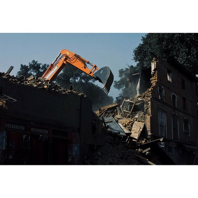 An excavator bringing down a building at Nagpokhari that was partially damaged by the earthquake. The army and police force are working together to safely bring down houses like these that may give up anytime causing further damage to lives and properties. May 26, 2015. Nepalearthquake Earthquake Nepal Kathmandu Nepalphotoproject Excavator Canoneos450D Instagramersoftheyear Instagramersoftheyear_nepal