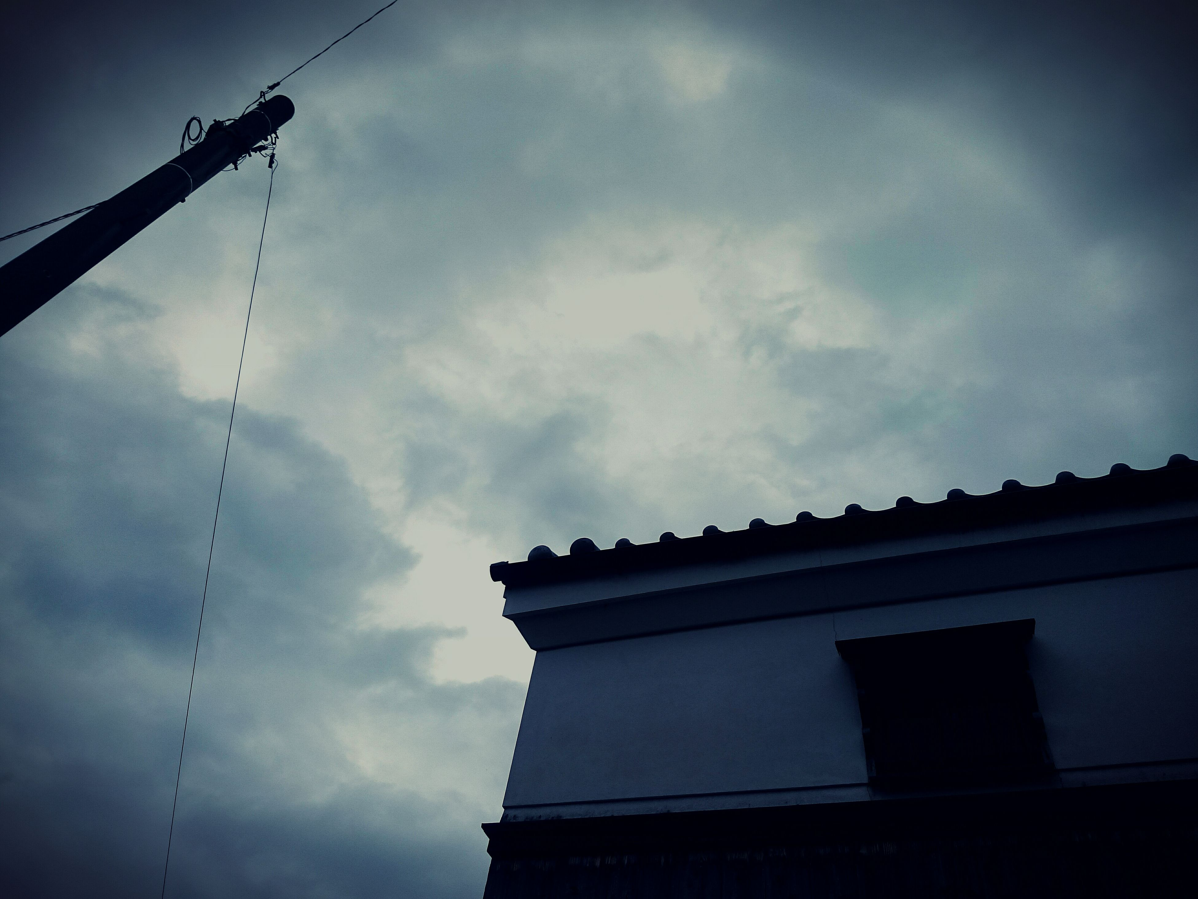 low angle view, architecture, sky, built structure, building exterior, cloud - sky, power line, cloudy, cable, building, street light, cloud, outdoors, lighting equipment, electricity, day, no people, city, high section, residential building