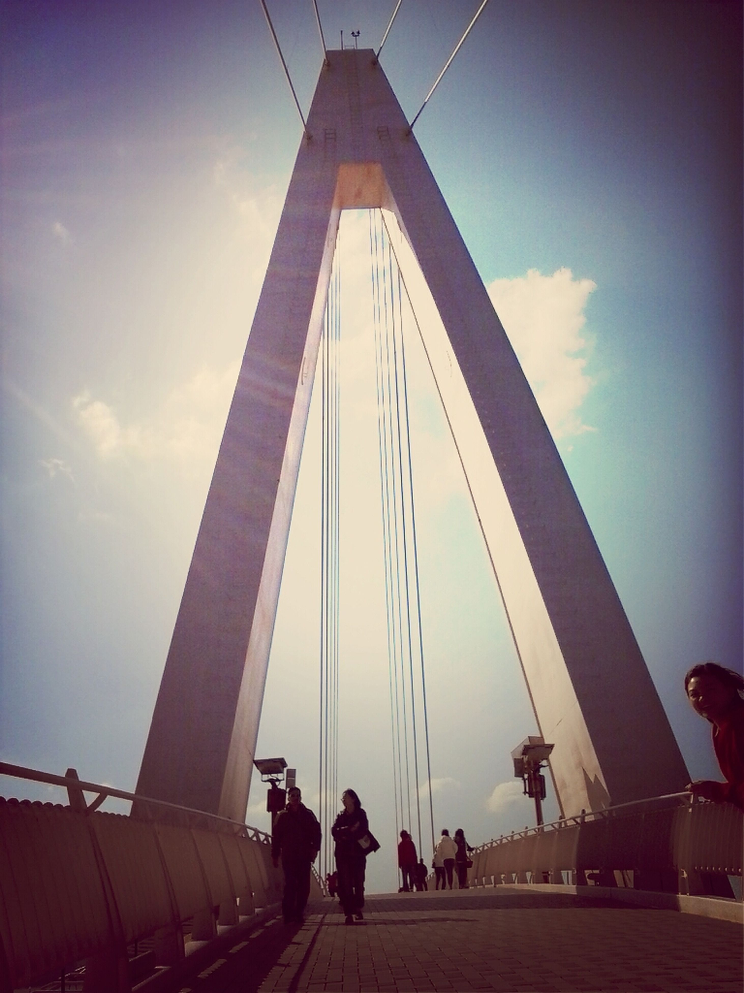 built structure, architecture, low angle view, sky, connection, silhouette, men, bridge - man made structure, engineering, suspension bridge, lifestyles, building exterior, leisure activity, city, travel destinations, cloud - sky, tall - high, modern, person
