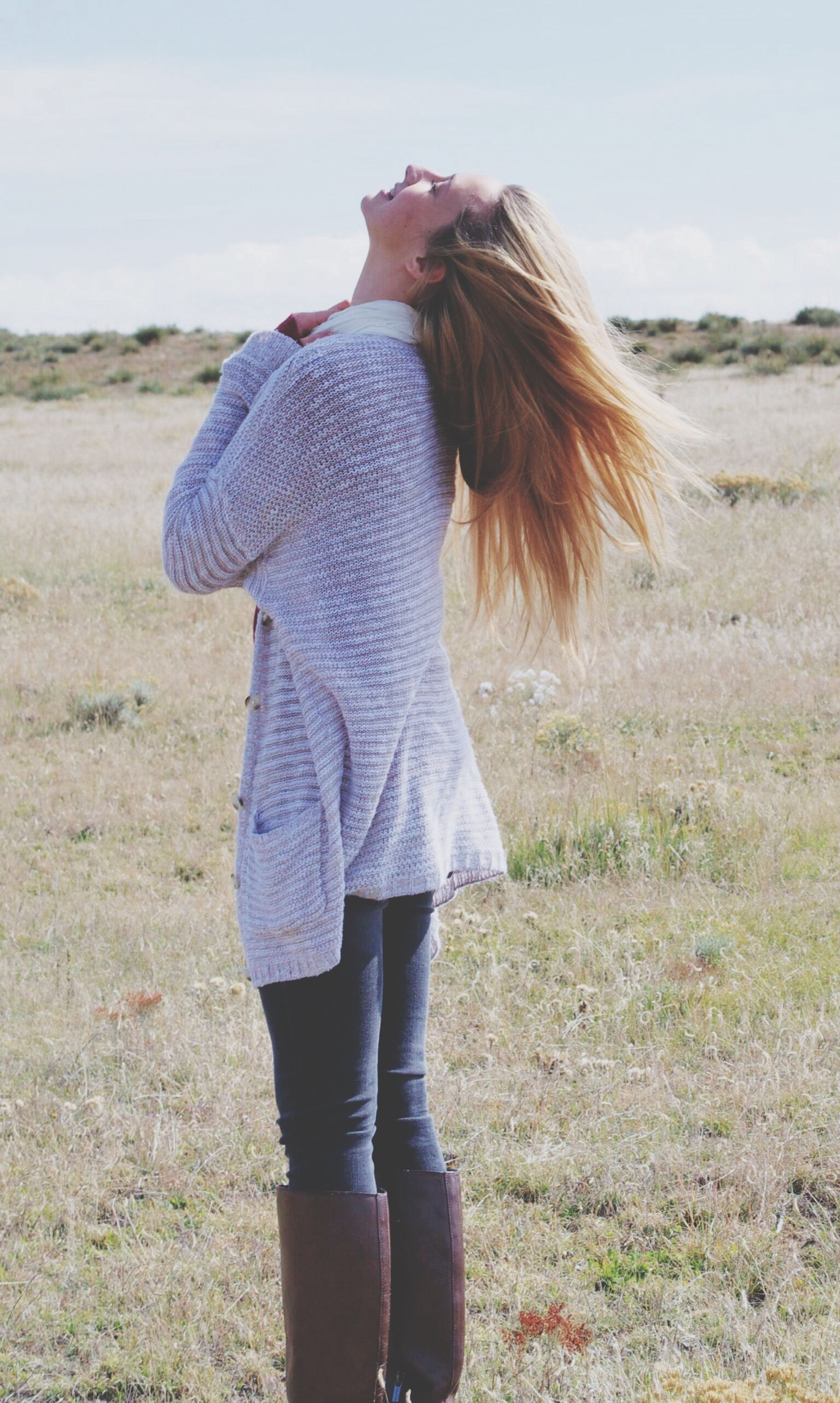 rear view, field, casual clothing, standing, grass, lifestyles, leisure activity, landscape, full length, sky, long hair, three quarter length, nature, focus on foreground, day, side view, person, outdoors