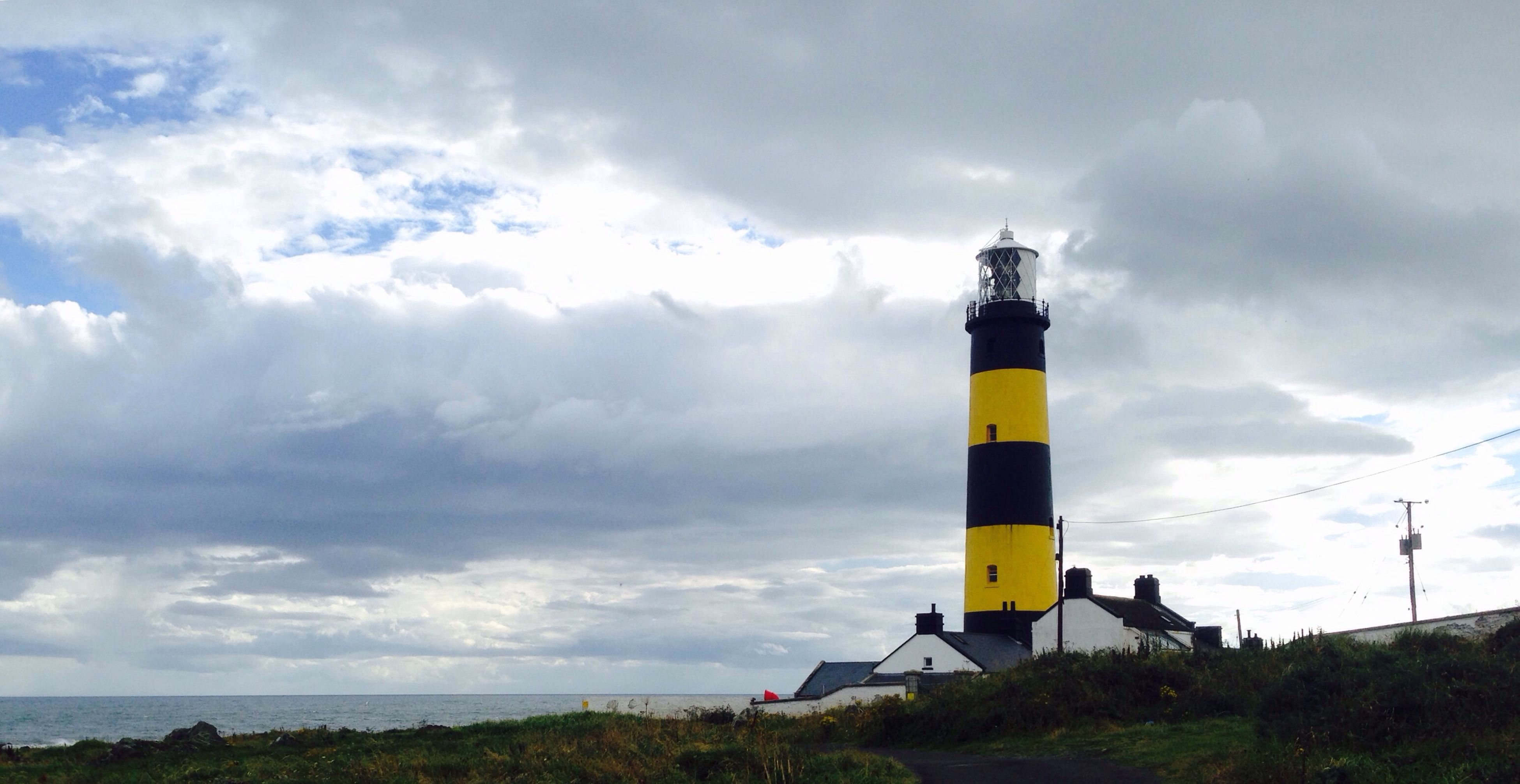 lighthouse, architecture, built structure, guidance, tower, building exterior, sky, protection, direction, yellow, cloud - sky, cloud, cloudy, field, outdoors, sea, nature, day, tall - high, tranquility, tranquil scene, tall, cloudscape, storm cloud, no people, scenics, green color