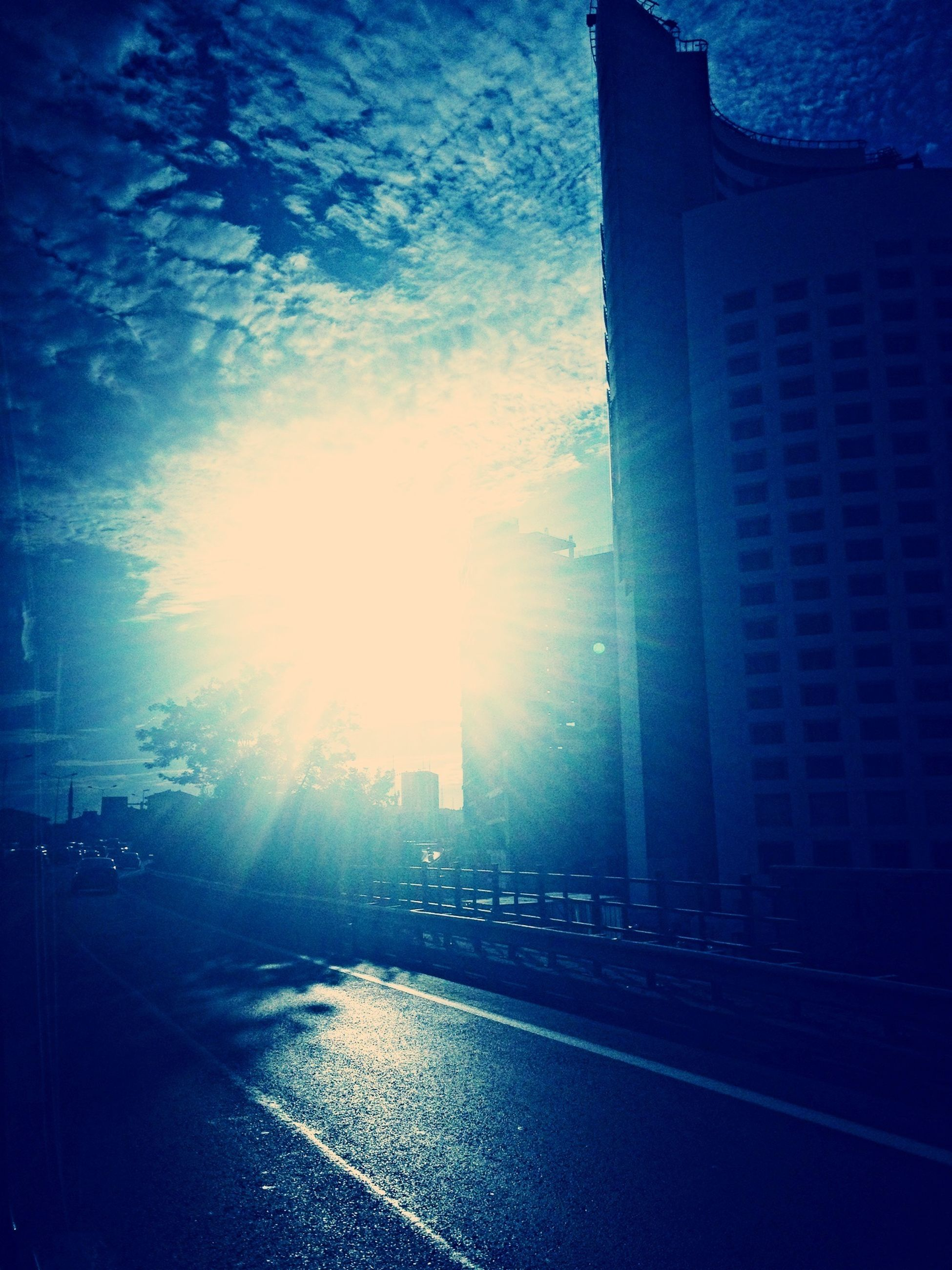 building exterior, architecture, built structure, sky, city, street, sunlight, road, sun, sunbeam, the way forward, lens flare, building, silhouette, blue, outdoors, cloud - sky, no people, transportation, road marking