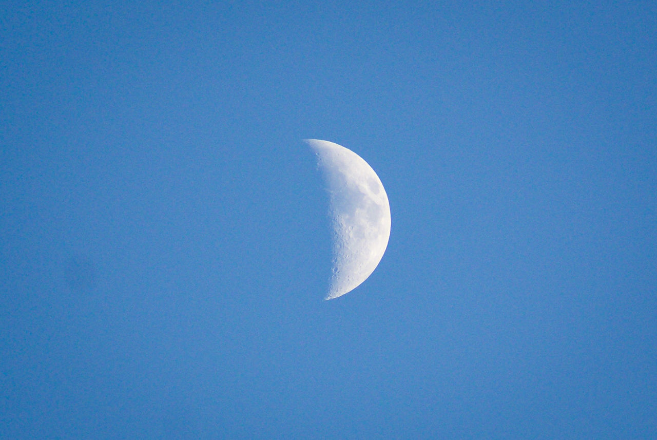 moon, nature, beauty in nature, low angle view, copy space, half moon, blue, astronomy, tranquil scene, clear sky, tranquility, scenics, planetary moon, moon surface, crescent, sky, outdoors, no people, space, sky only, space exploration, night