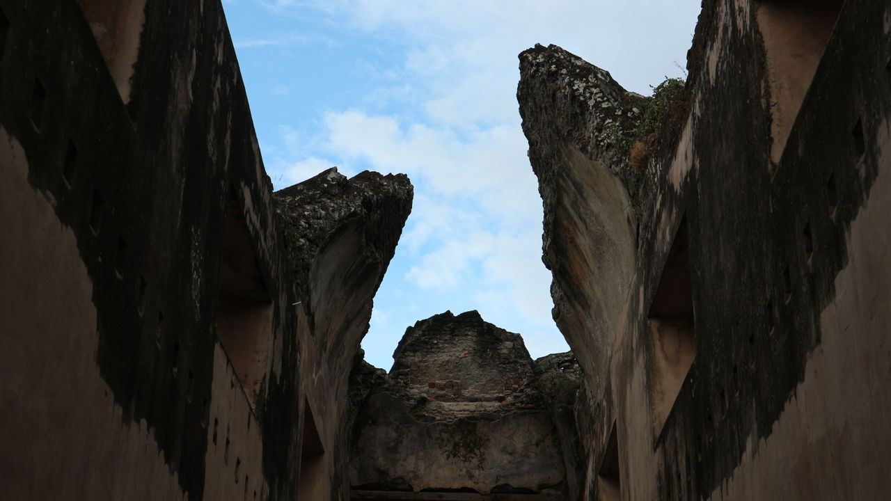 low angle view, sky, day, architecture, cloud - sky, rock - object, built structure, no people, nature, history, outdoors, mountain, beauty in nature, ancient civilization