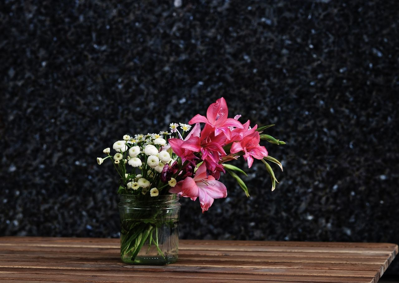 Flowers In Vase On Wooden Table