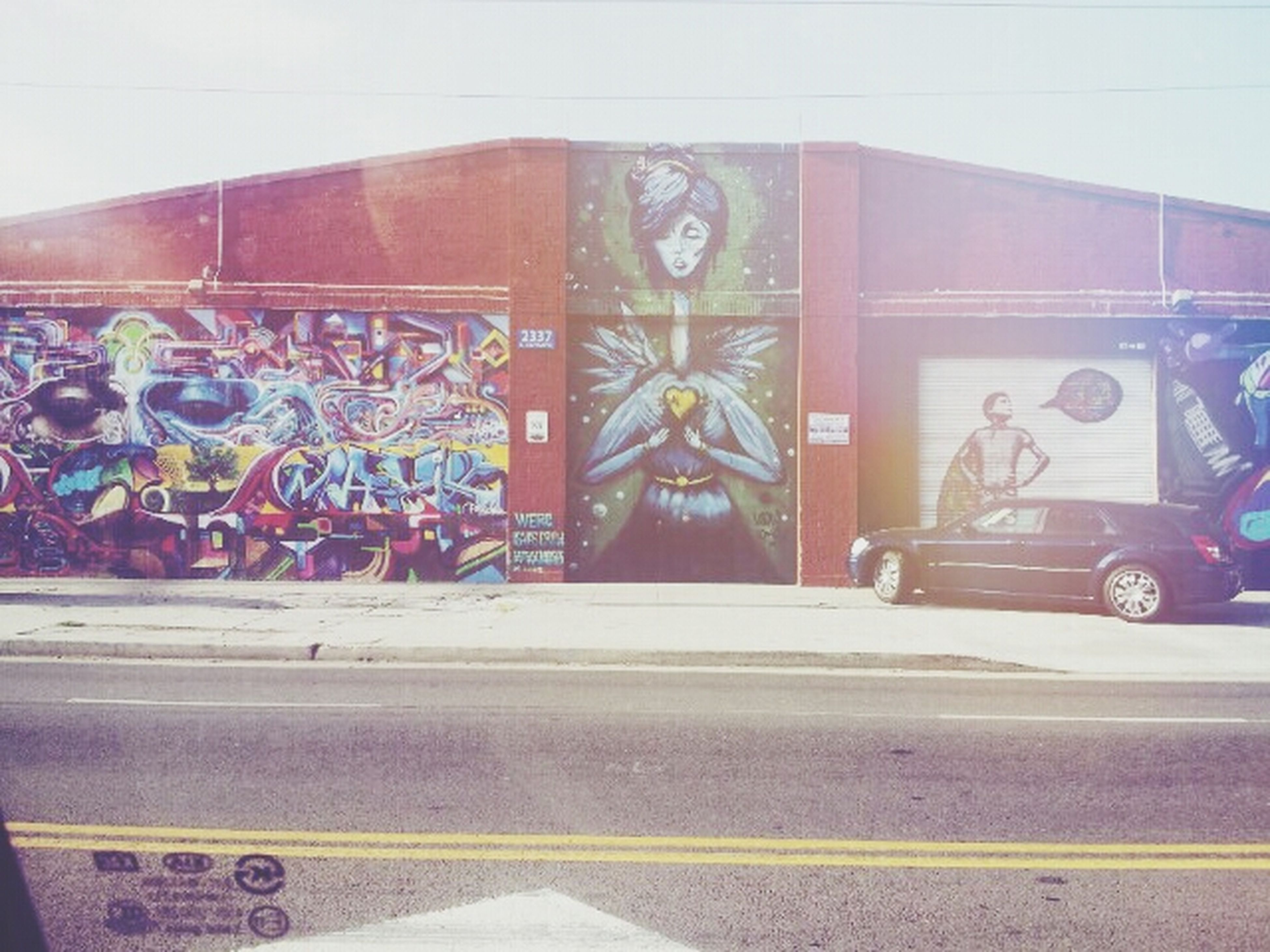 art and craft, art, creativity, graffiti, architecture, built structure, human representation, street, building exterior, transportation, text, road, land vehicle, wall - building feature, multi colored, car, street art, western script, outdoors