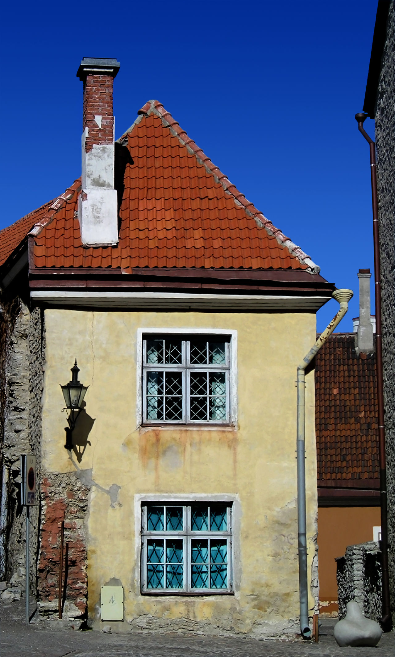 A run down house in the old town of Tallinn, Estonia with a statue of a duck next to it. Blue Sky Duck Statues Exposed Bricks House Run Down Places Tallinn Estonia Tallinn Old Town
