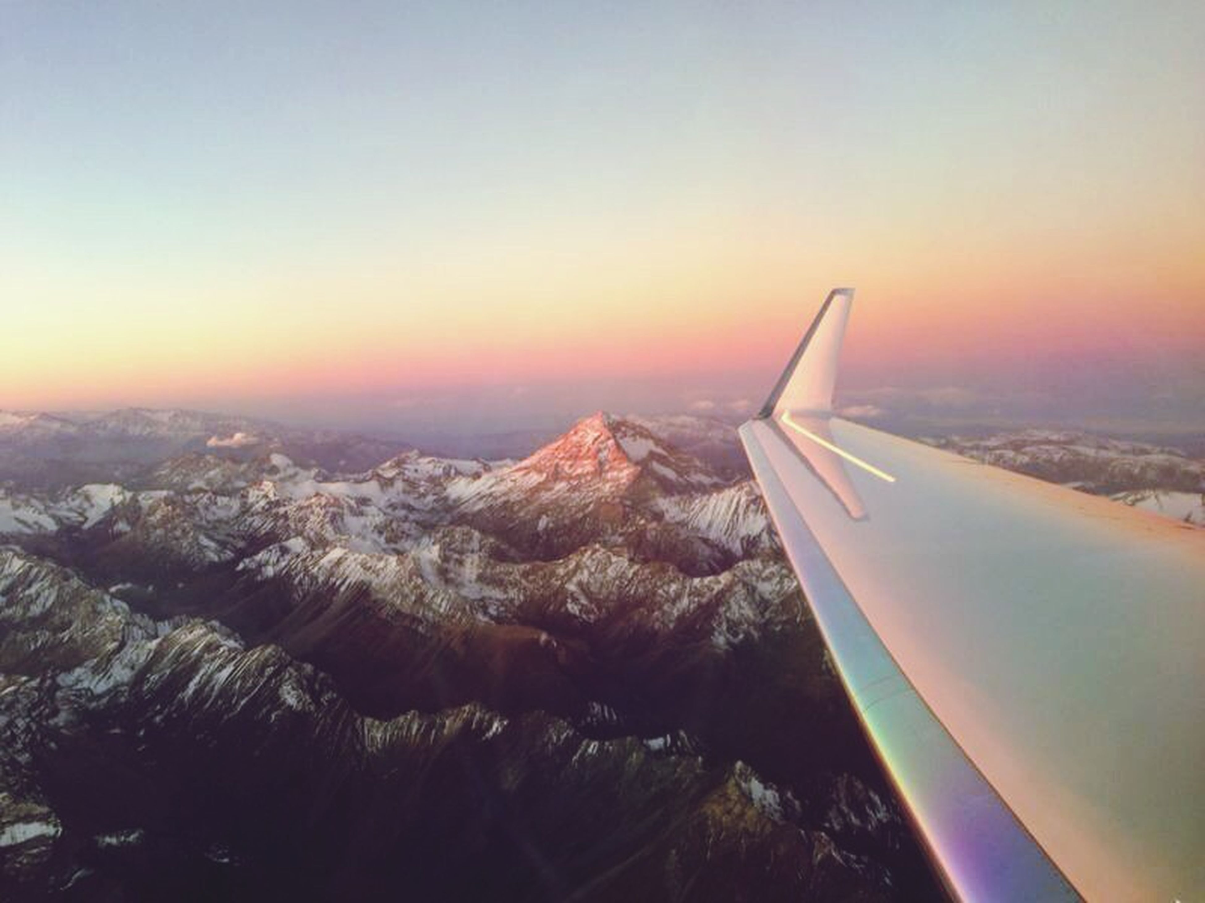 aircraft wing, airplane, air vehicle, sunset, flying, cropped, transportation, part of, landscape, sky, scenics, aerial view, mode of transport, beauty in nature, nature, clear sky, orange color, travel, mid-air, sun