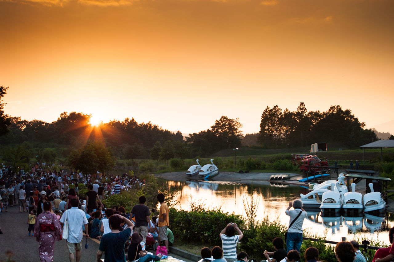 sunset, large group of people, enjoyment, tree, nature, outdoors, leisure activity, sunlight, real people, sky, women, togetherness, clear sky, crowd, beauty in nature, water, people, day