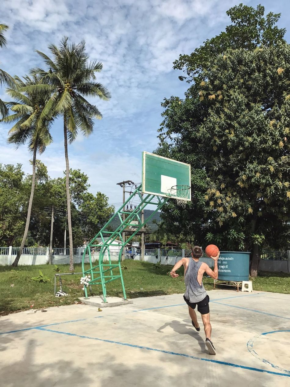 Sport Playing One Man Only Real People Young Men Palm Tree One Person Men Only Tree Court Playground Holding Lifestyles Basketball Hoop Competitive Sport Day Full Length Sportsman Basketball - Sport Basketball Hoop Ball Athleisure Athlete Healthy Lifestyle Cloud - Sky